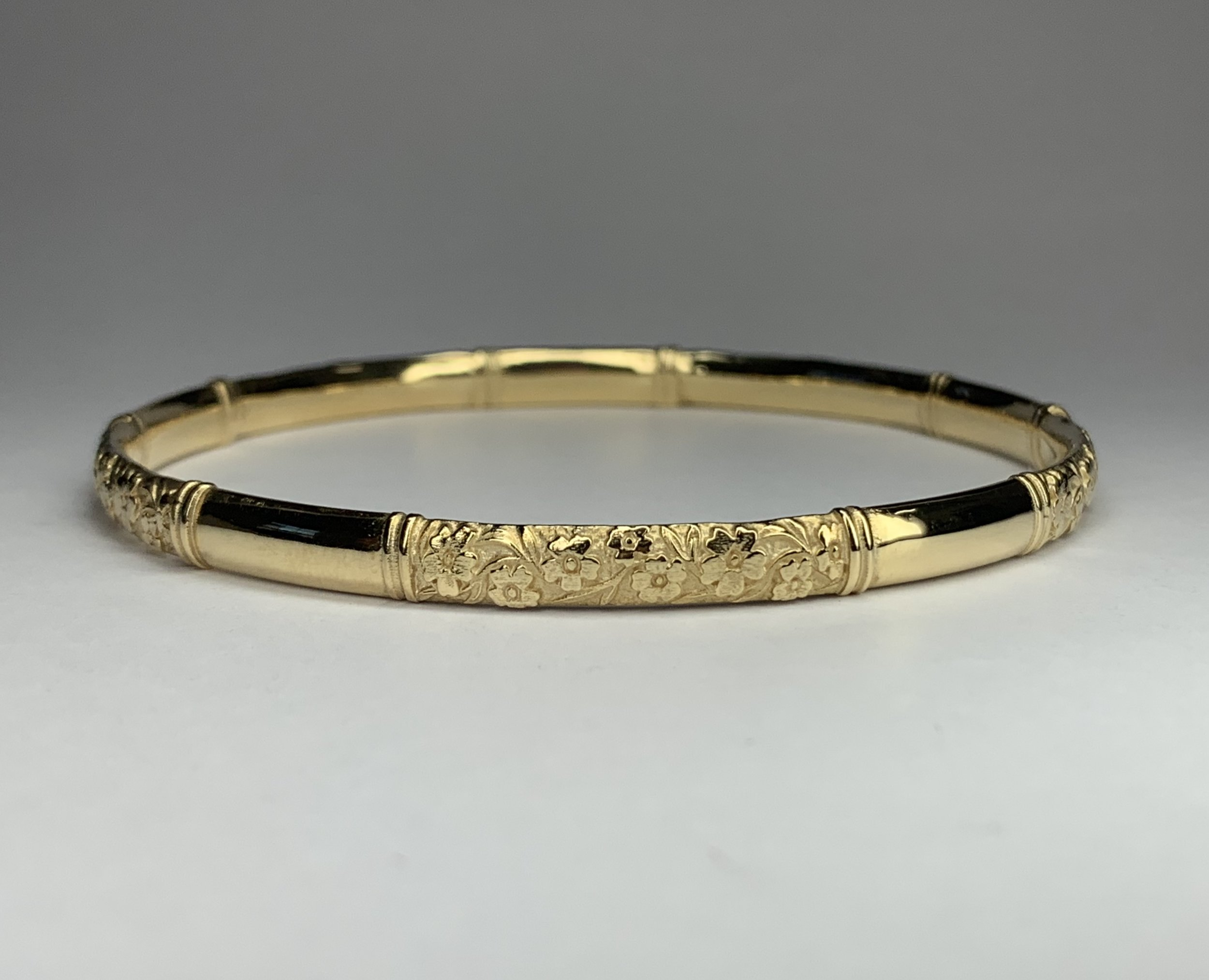 Yellow gold slave bangle with raised forget me not sections alternating with high polished sections. Made in Chichester, England.