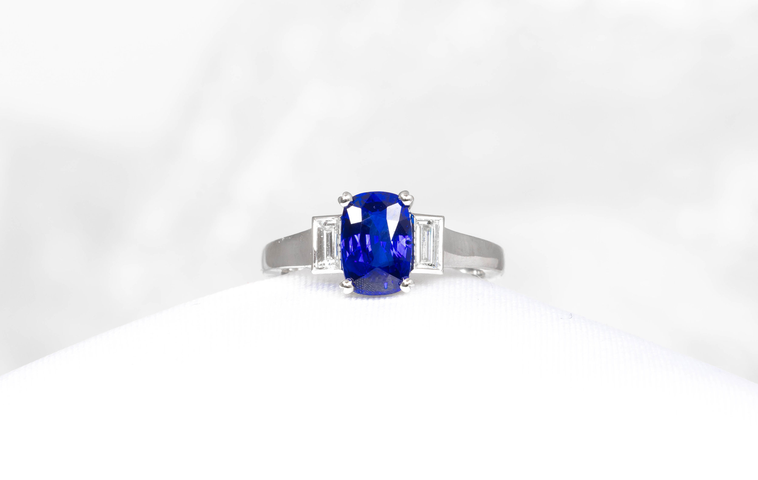 Platinum mounted oblong cushion cut Sri Lankan sapphire and baguette diamond set 3 stone ring. Made in Chichester, England.