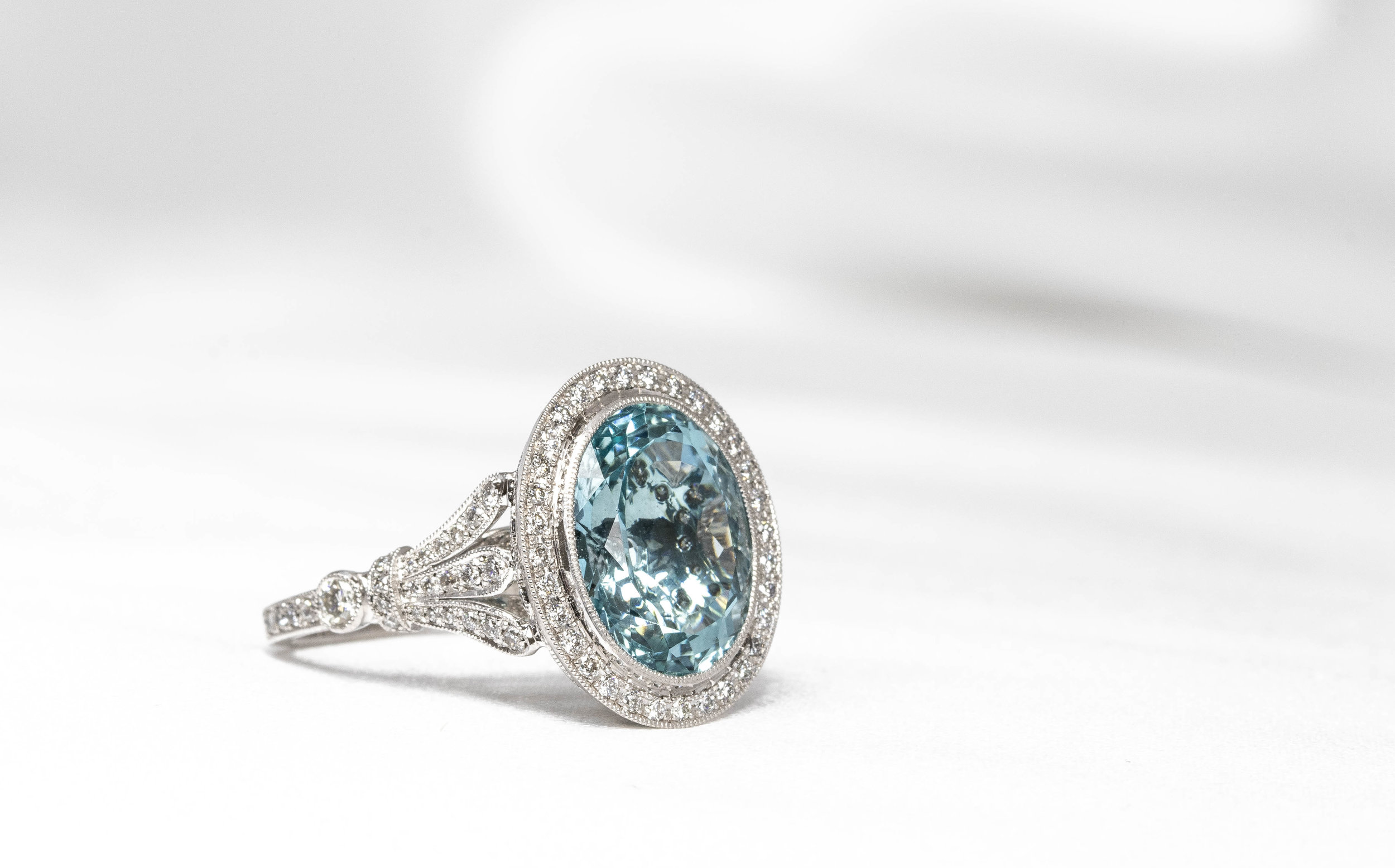 Platinum mounted early C20th style aquamarine and diamond oval cluster ring. Made in Chichester, England.