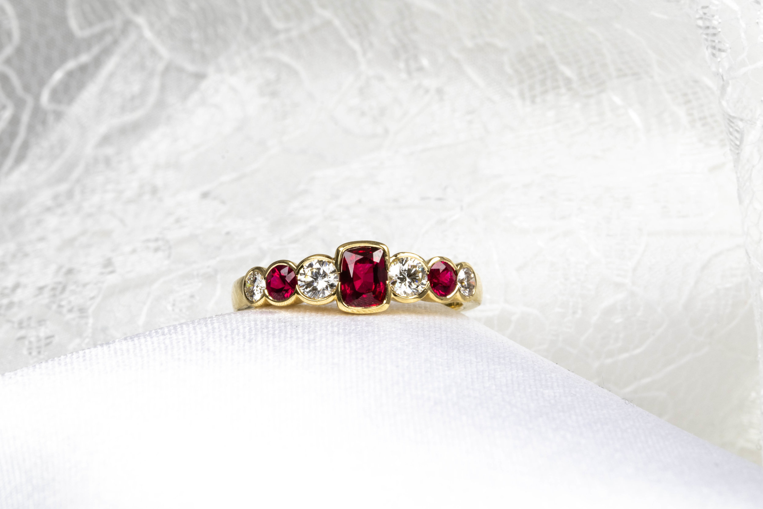 18ct yellow gold ruby and diamond rub-over set 7 stone ring. Made in Chichester, England.