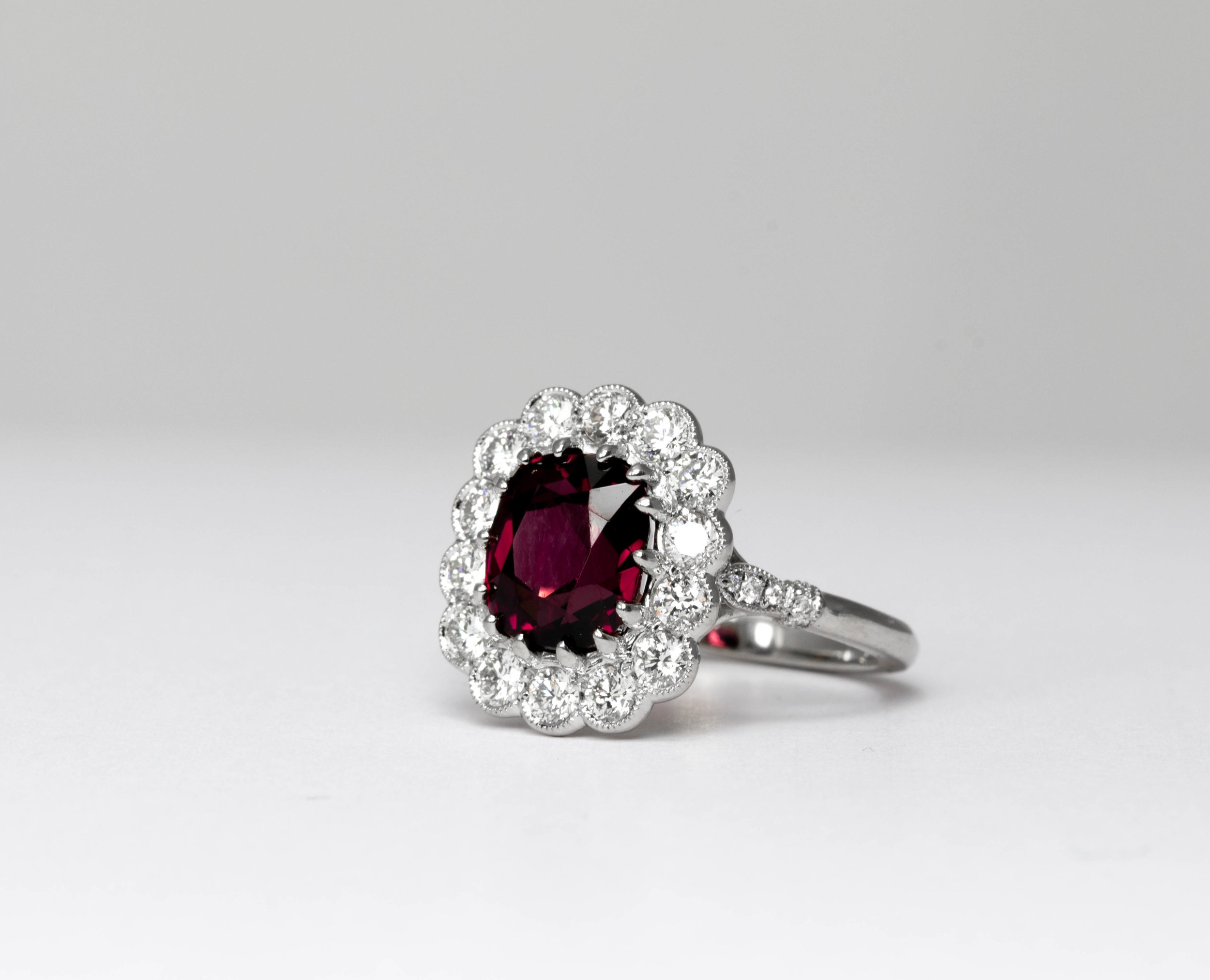 Platinum mounted, diamond and cushion cut grape garnet Edwardian style cluster ring. Made in Chichester, England.