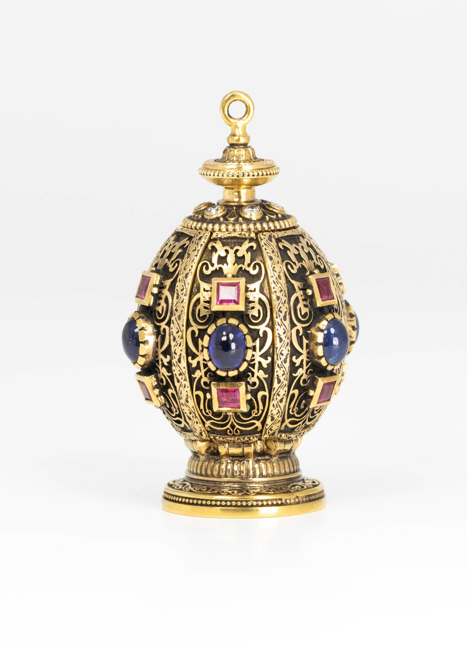 The pomander in the closed position showing the square cut rubies, cabouchon sapphires and almost visible, the diamond set top.