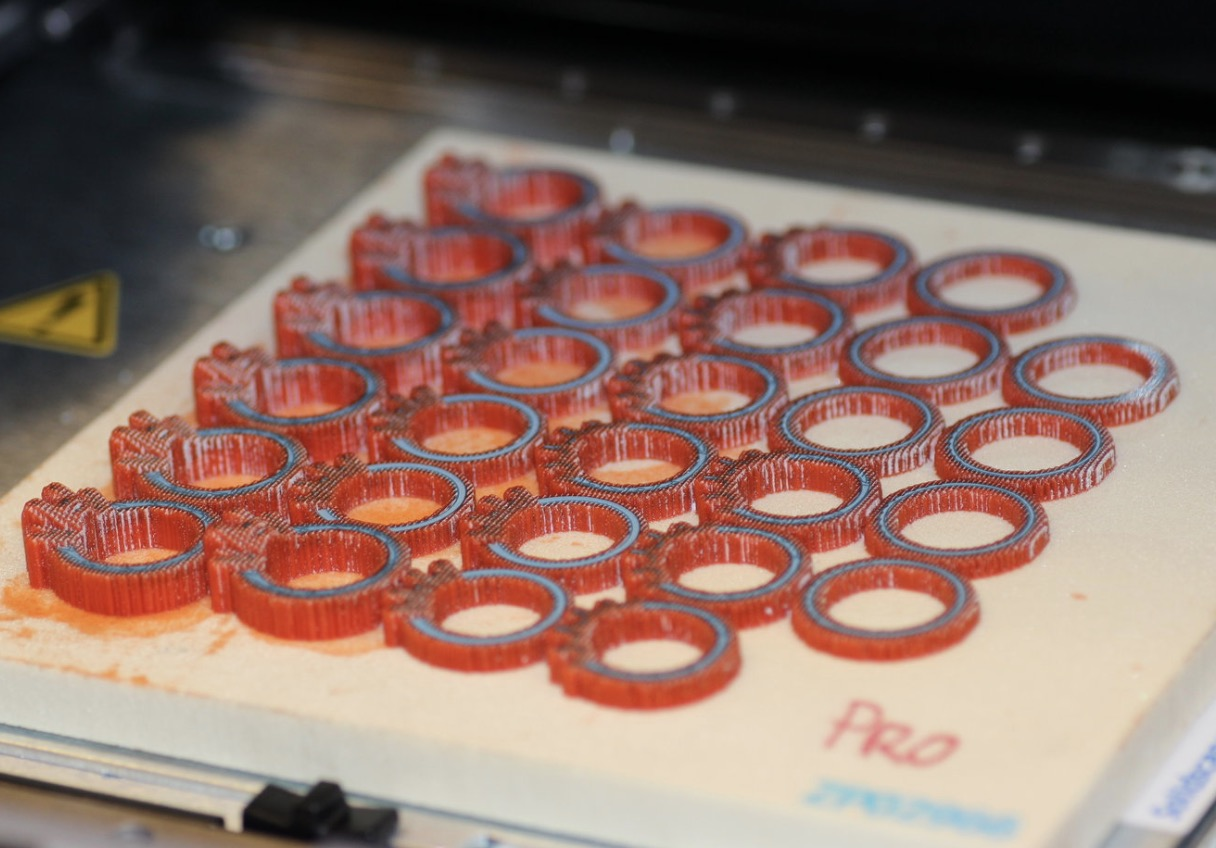A build plate full up with printed ring models. The blue wax is the actual model and the red wax is there to support and protect the model as it is being built.