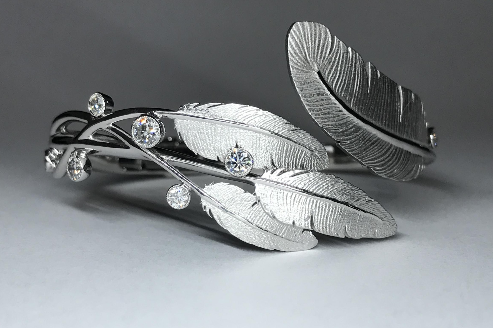 One-of-a-kind 18ct white gold feather and diamond set hinged bespoke bangle. Made in Chichester, England.
