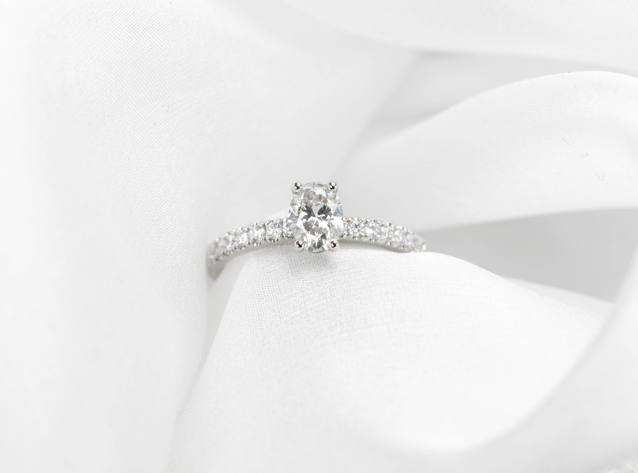 Copy of Platinum mounted oval diamond set ring with diamond set shoulders. Made in Chichester, England.