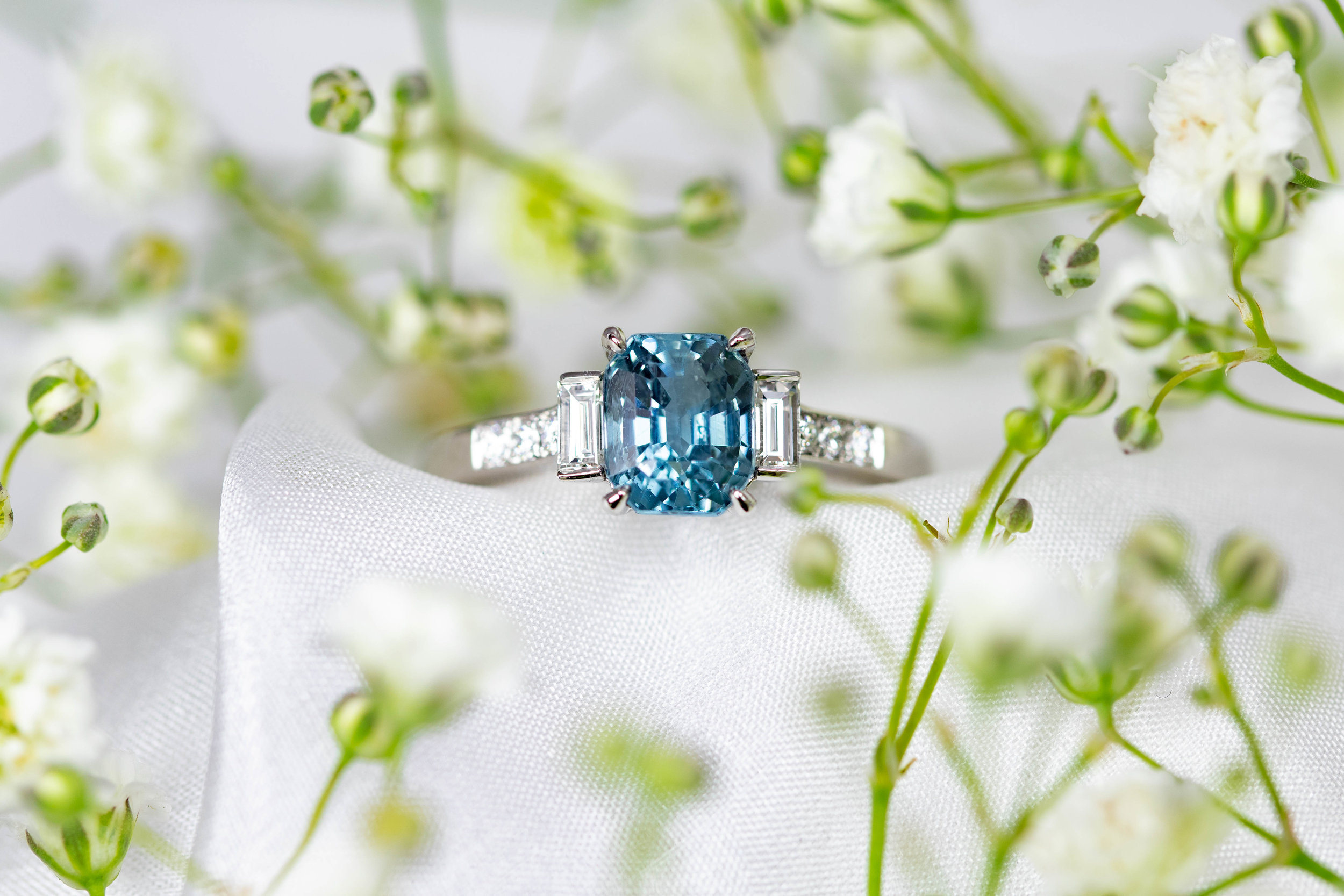 Platinum mounted teal sapphire and diamond baguette shoulder ring. Made in Chichester, England.
