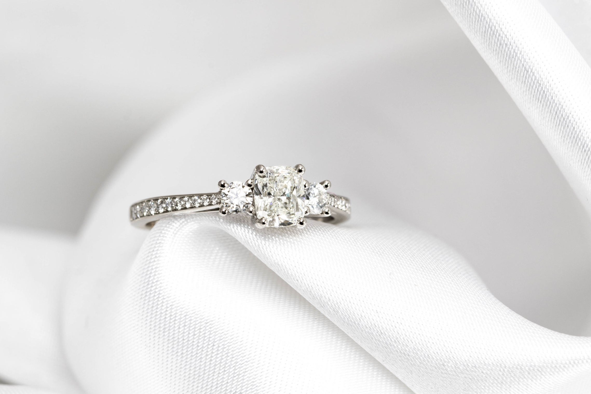 Platinum mounted 0.70ct cushion cut and round brilliant cut diamond 3 stone ring with grain set diamond shoulders. Made in Chichester, England.