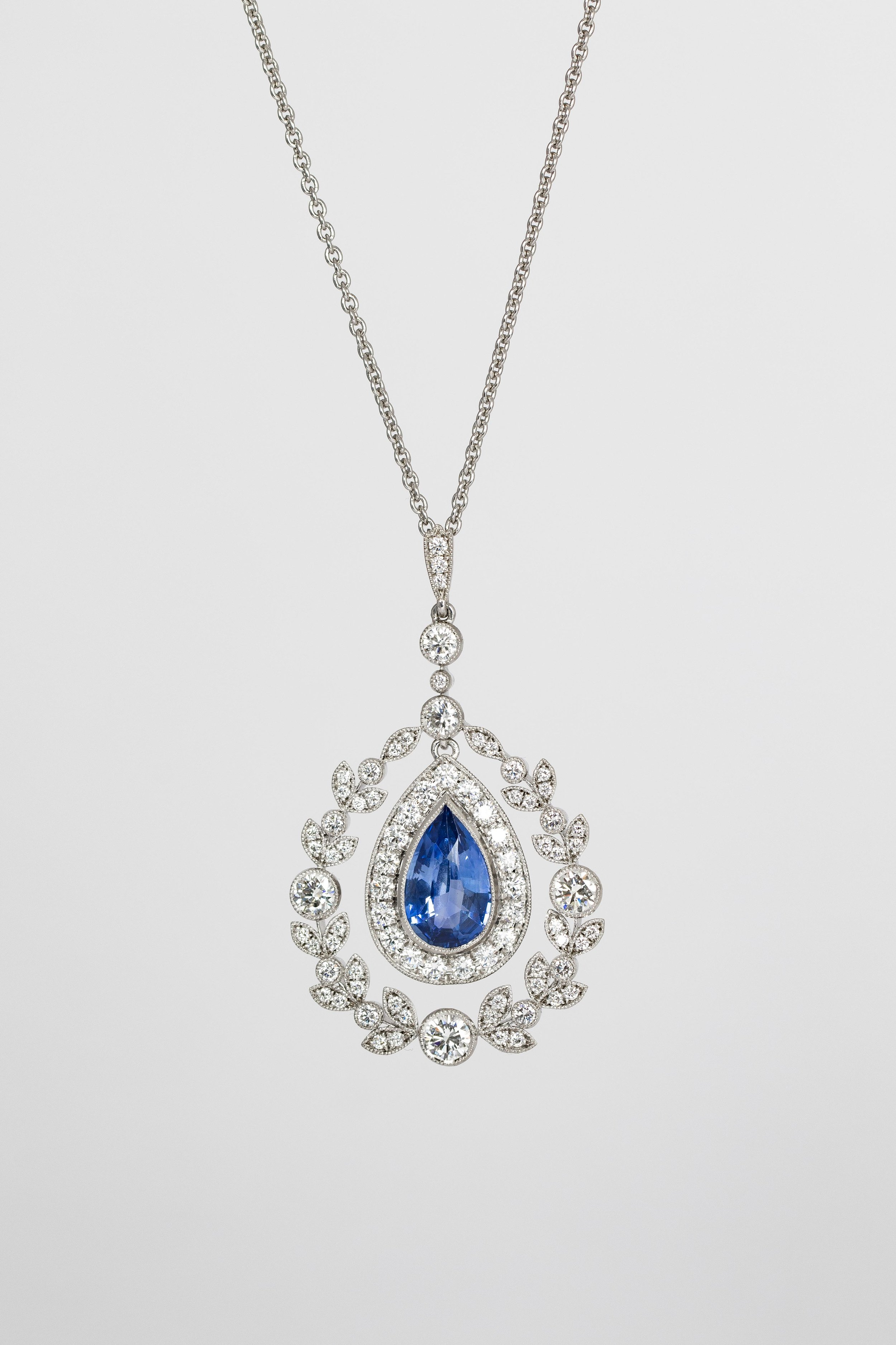 18ct white gold mounted pear-shaped sapphire and diamond set Edwardian style pendant. Made in Chichester, England.