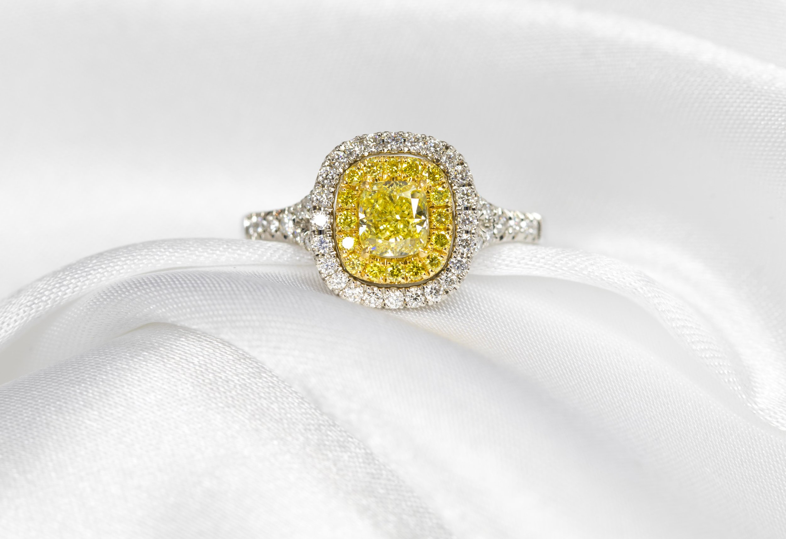 Platinum mounted diamond and natural yellow diamond cushion-shaped cluster ring. Made in Chichester, England.