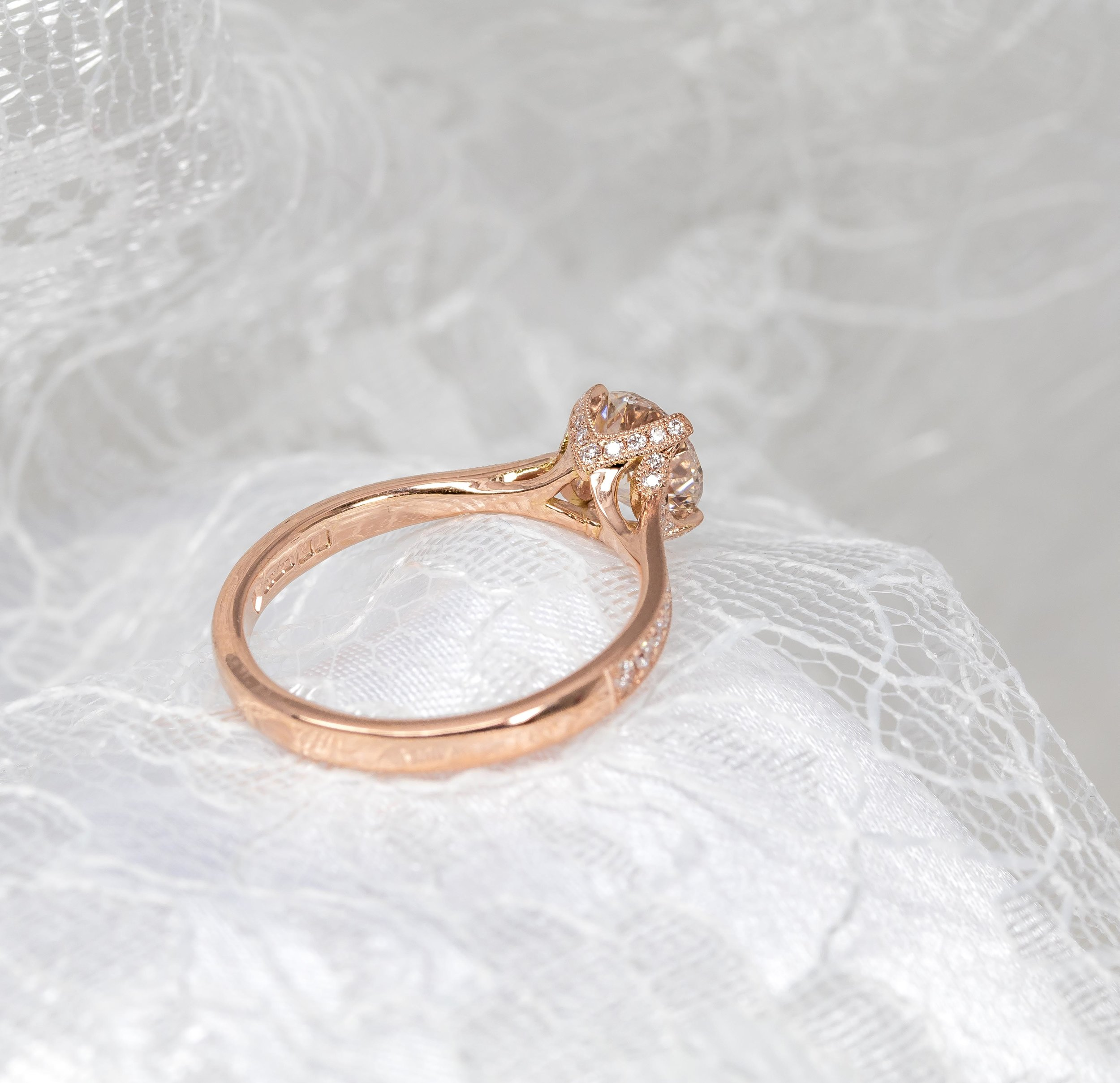 18ct rose gold mounted diamond solitaire with grain set diamond claws and shoulders. Made in Chichester, England.