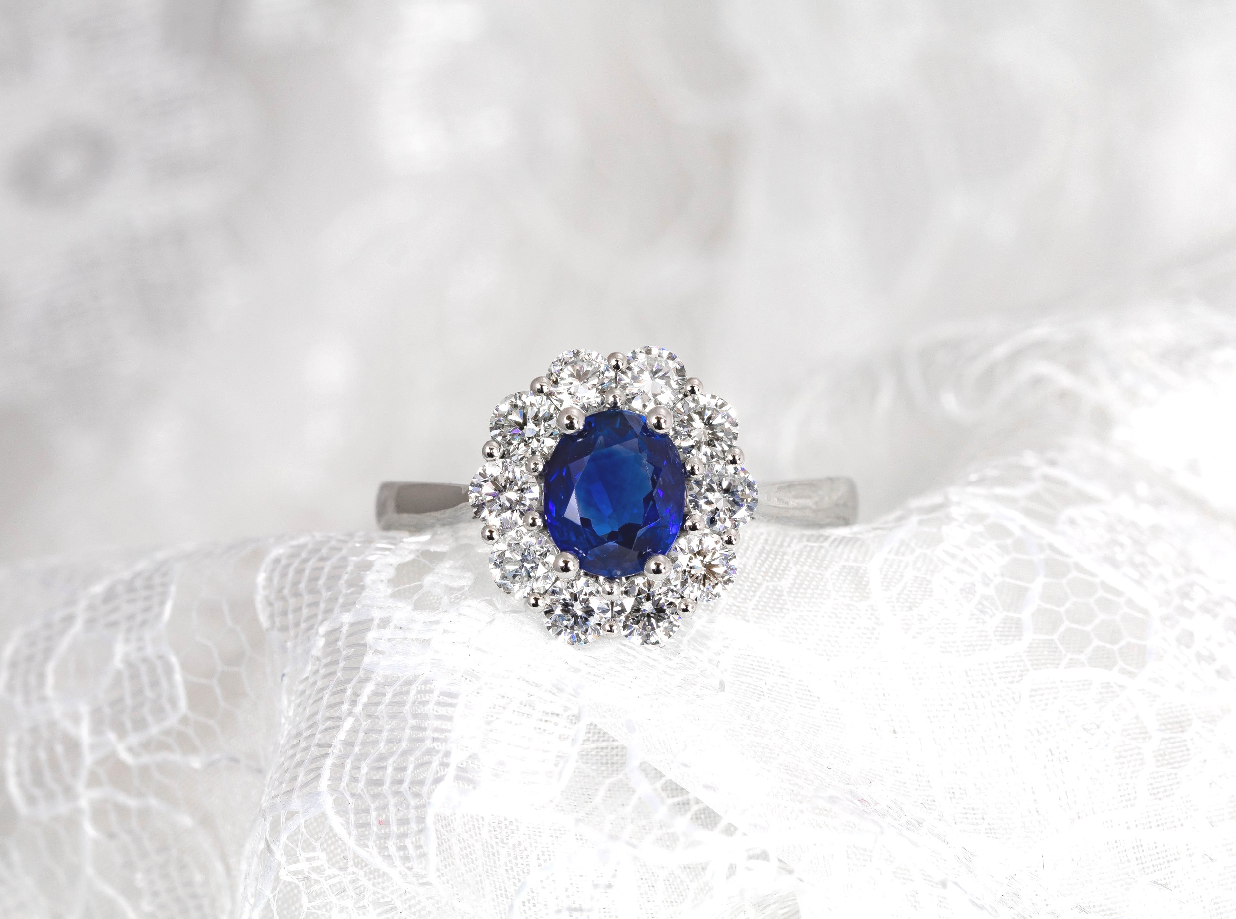 Platinum mounted 1.42ct Sri Lankan sapphire and diamond oval cluster ring. Made in Chichester, England.