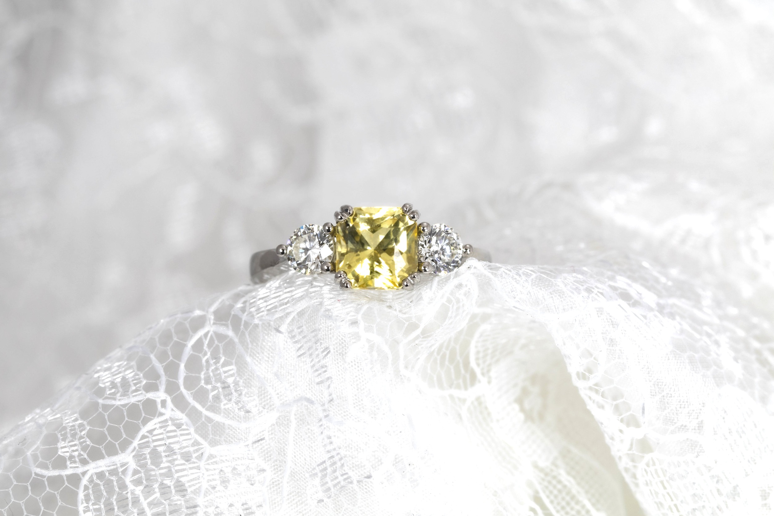 Platinum mounted 2.03ct Yellow sapphire and diamond set 3 stone ring with grain set diamond bezels. Made in Chichester, England.