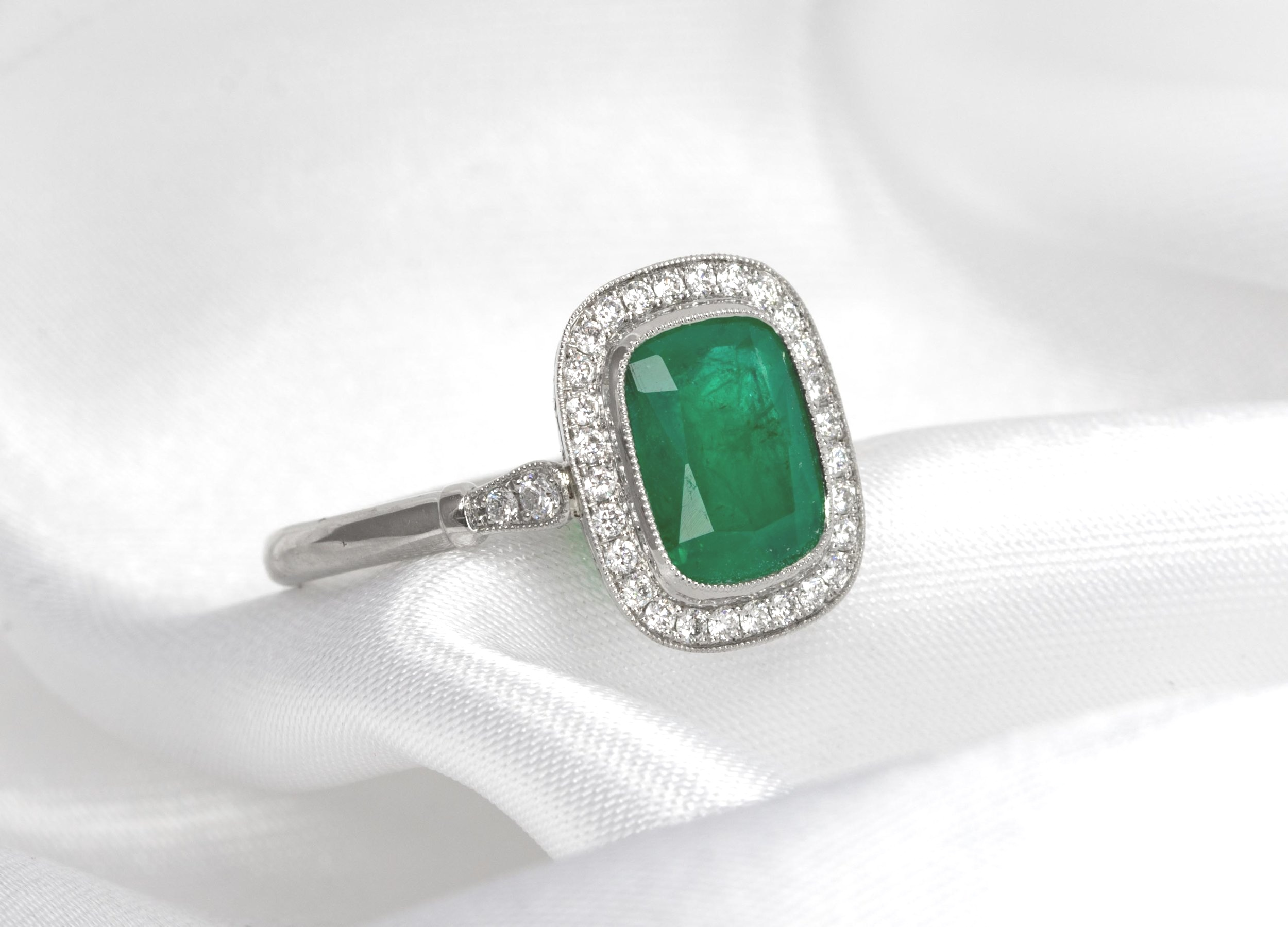 Oblong cushion cut emerald and diamond 1920's style cluster ring with millegrain edge decoration. Made in Chichester, England