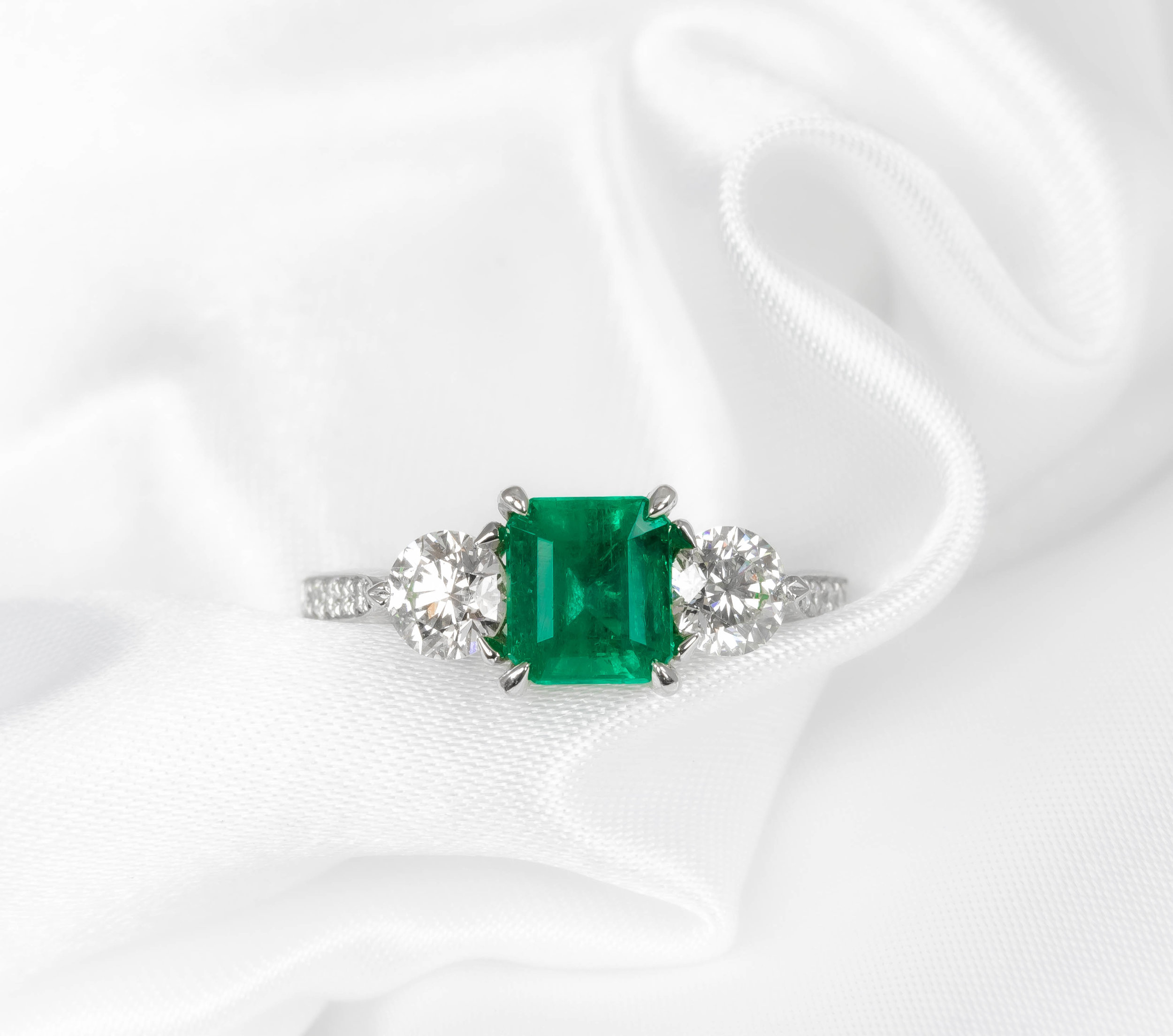 Platinum mounted, emerald and diamond three stone claw set ring with grain set diamond shoulders. Made in Chichester, England.