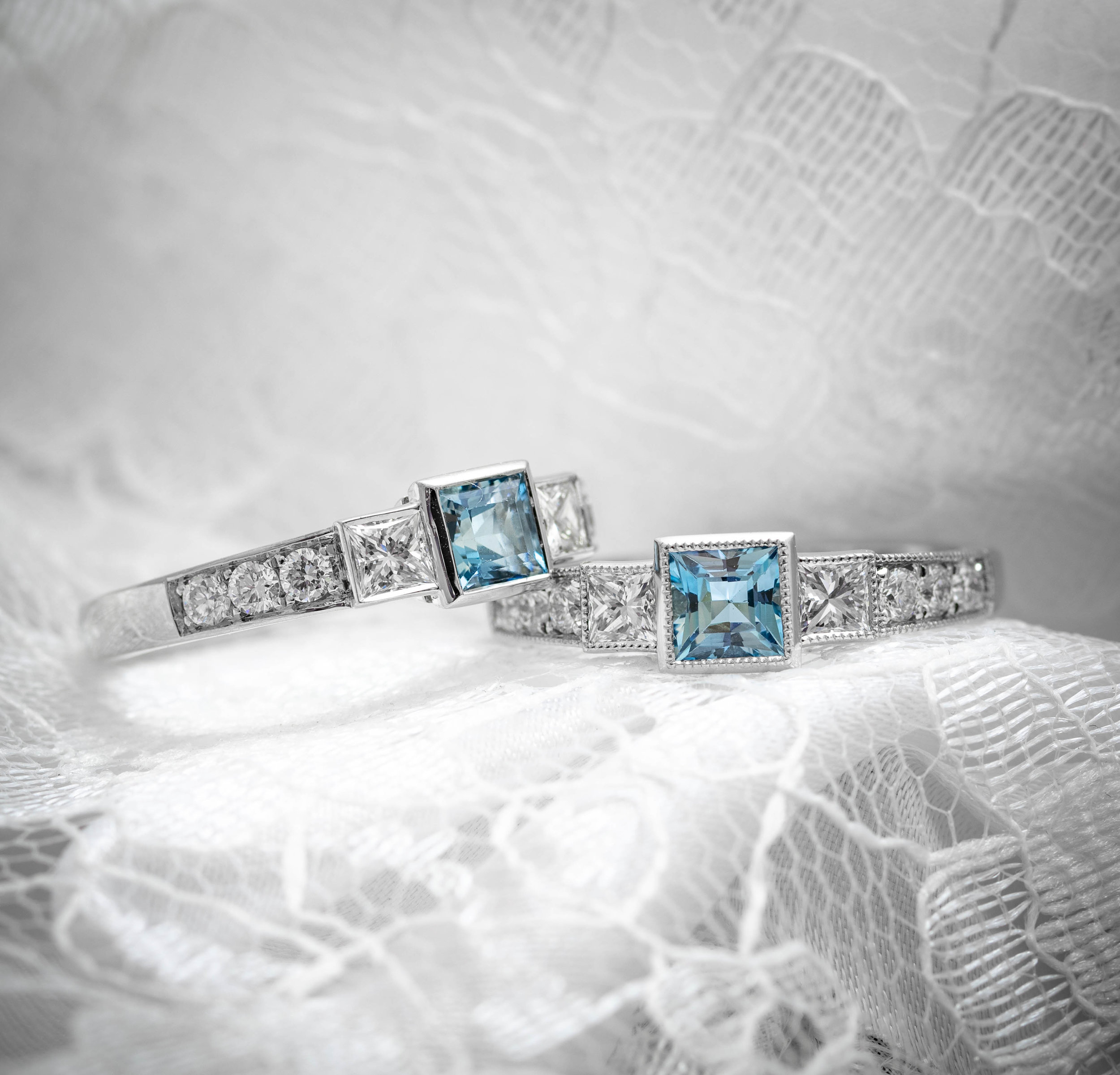 Platinum mounted, aquamarine and diamond set rings. One with plain edged collets and the same ring with millegrain edge decoration. Made in Chichester, England.
