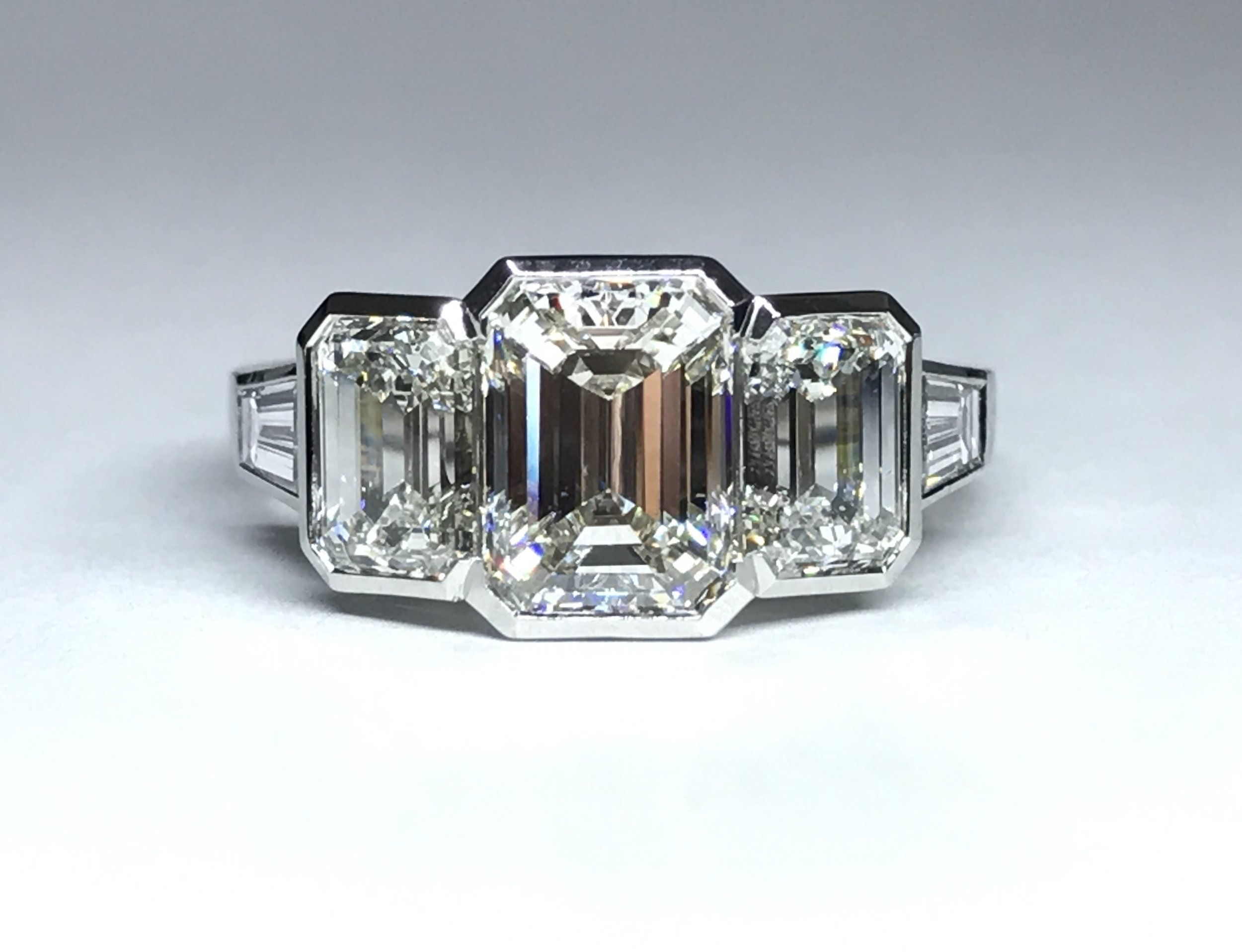 Platinum mounted emerald cut diamond, rub-over set 3 stone with tapered baguette diamond set shoulders. Made in Chichester, England..