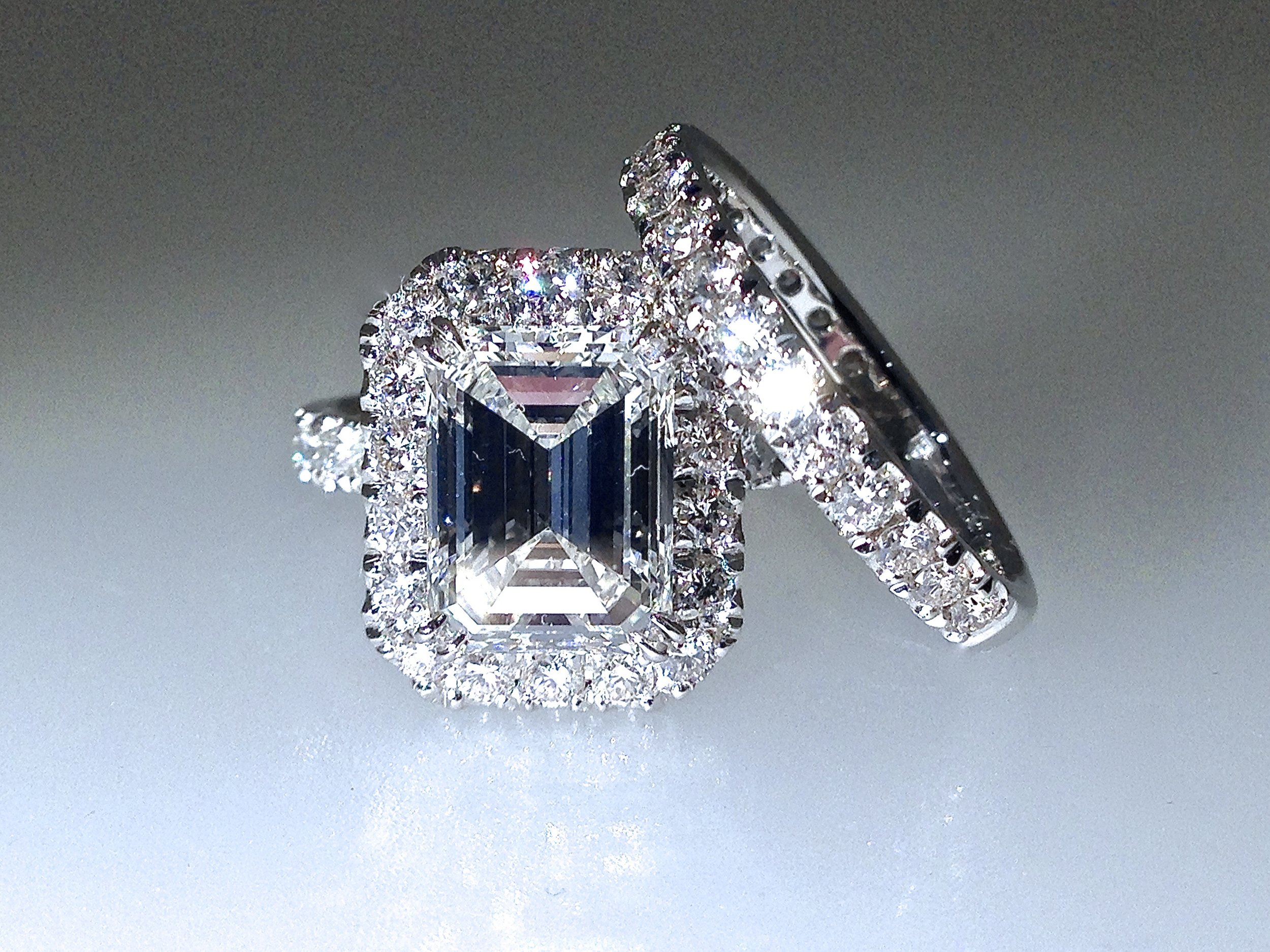 Platinum mounted matching emerald cut halo cluster and diamond band ring. Made in Chichester, England.