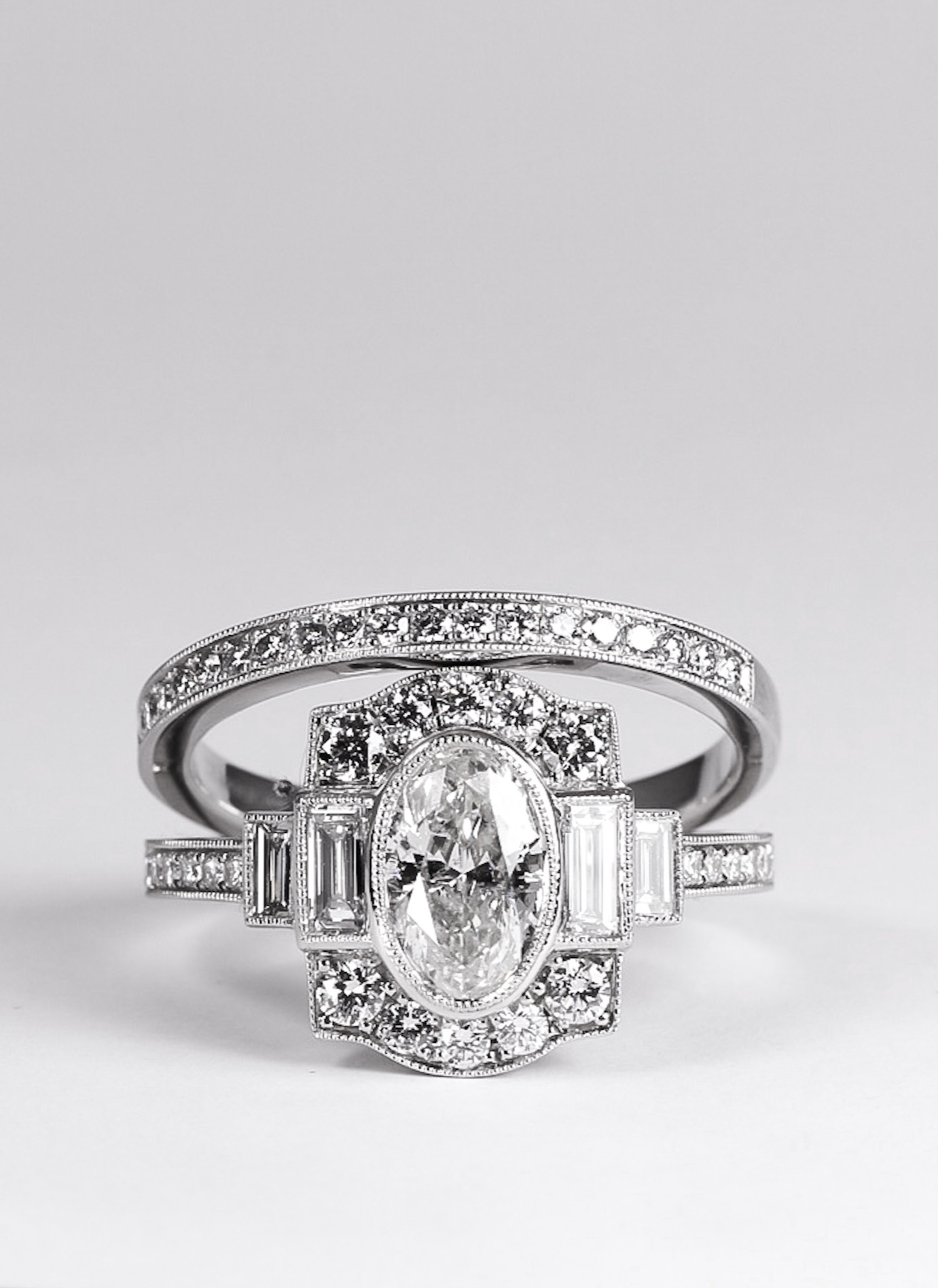 Platinum mounted oval diamond set Art Deco style cluster ring with baguette diamond stepped shoulders . Made in Chichester, England.