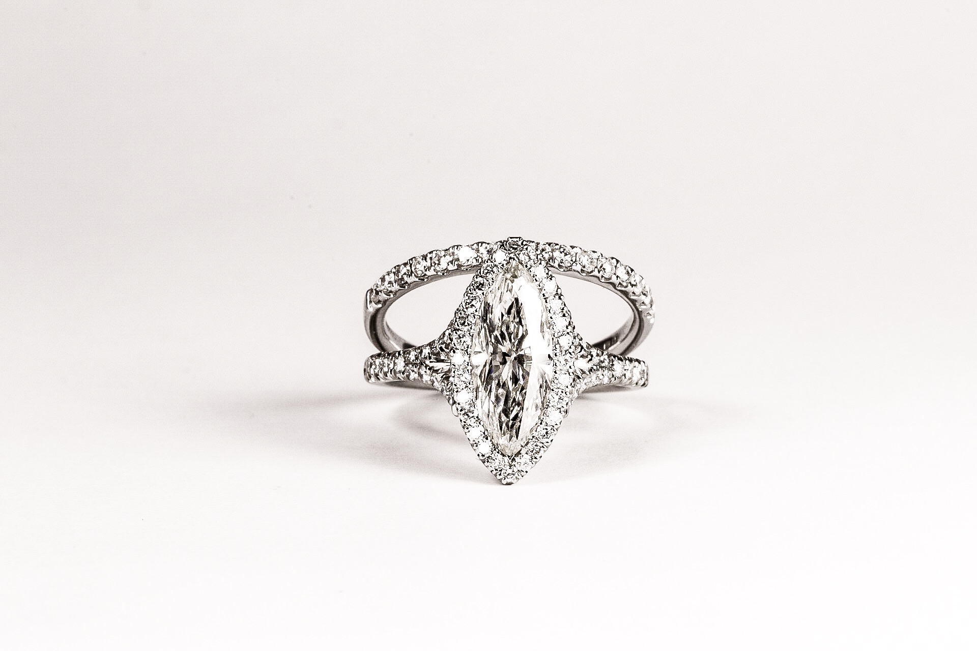 Platinum mounted marquise diamond set halo cluster ring with diamond set split shoulders. Made in Chichester, England.