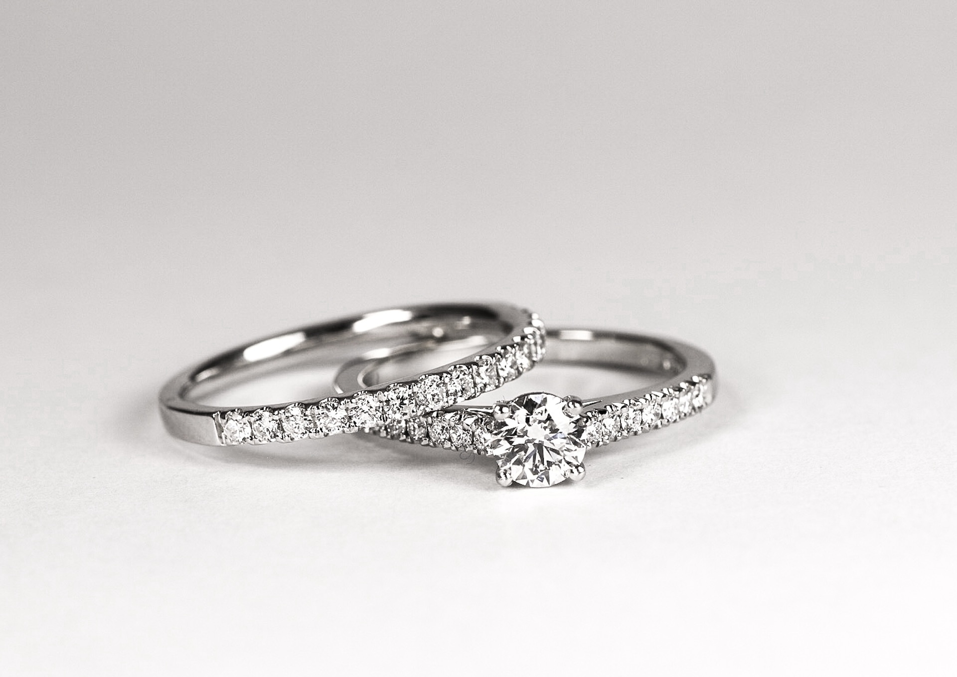 Platinum mounted solitaire with cut-away diamond set shoulders and matching band ring. Made in Chichester, England.
