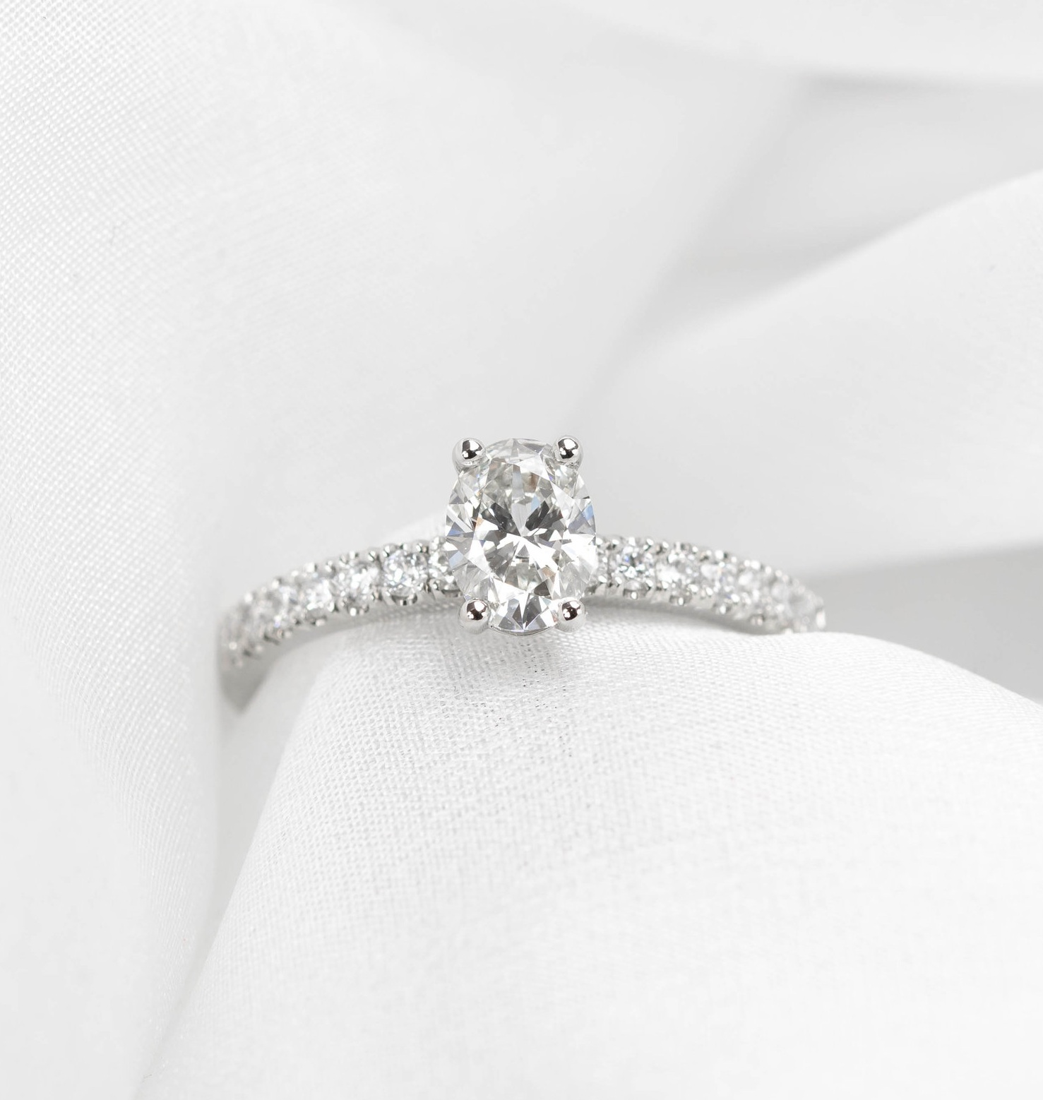 Platinum mounted oval diamond set ring with diamond set shoulders. Made in Chichester, England.