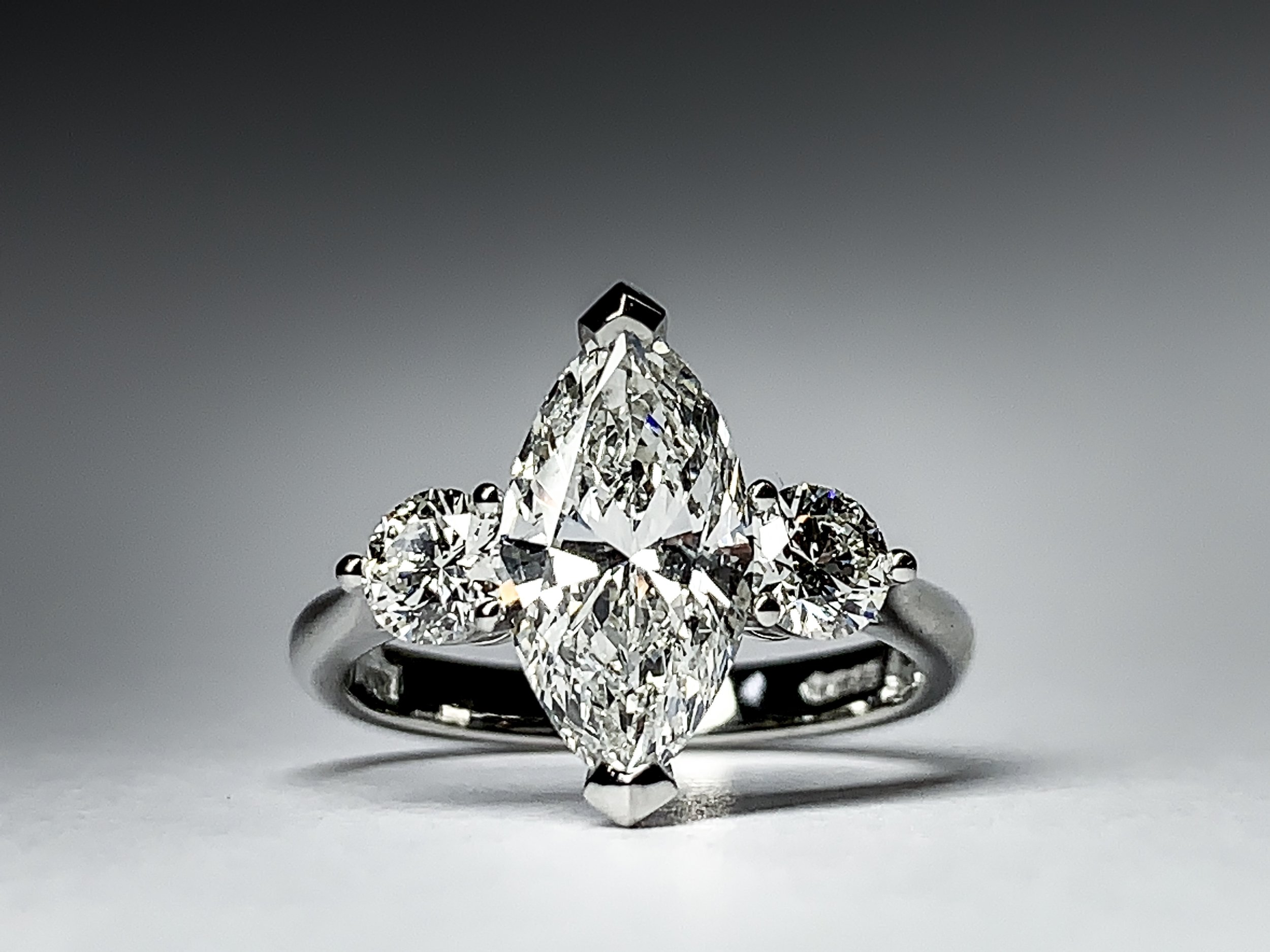 Platinum mounted 1.69ct marquise and round diamond 3 stone claw set ring. Made in Chichester, England.