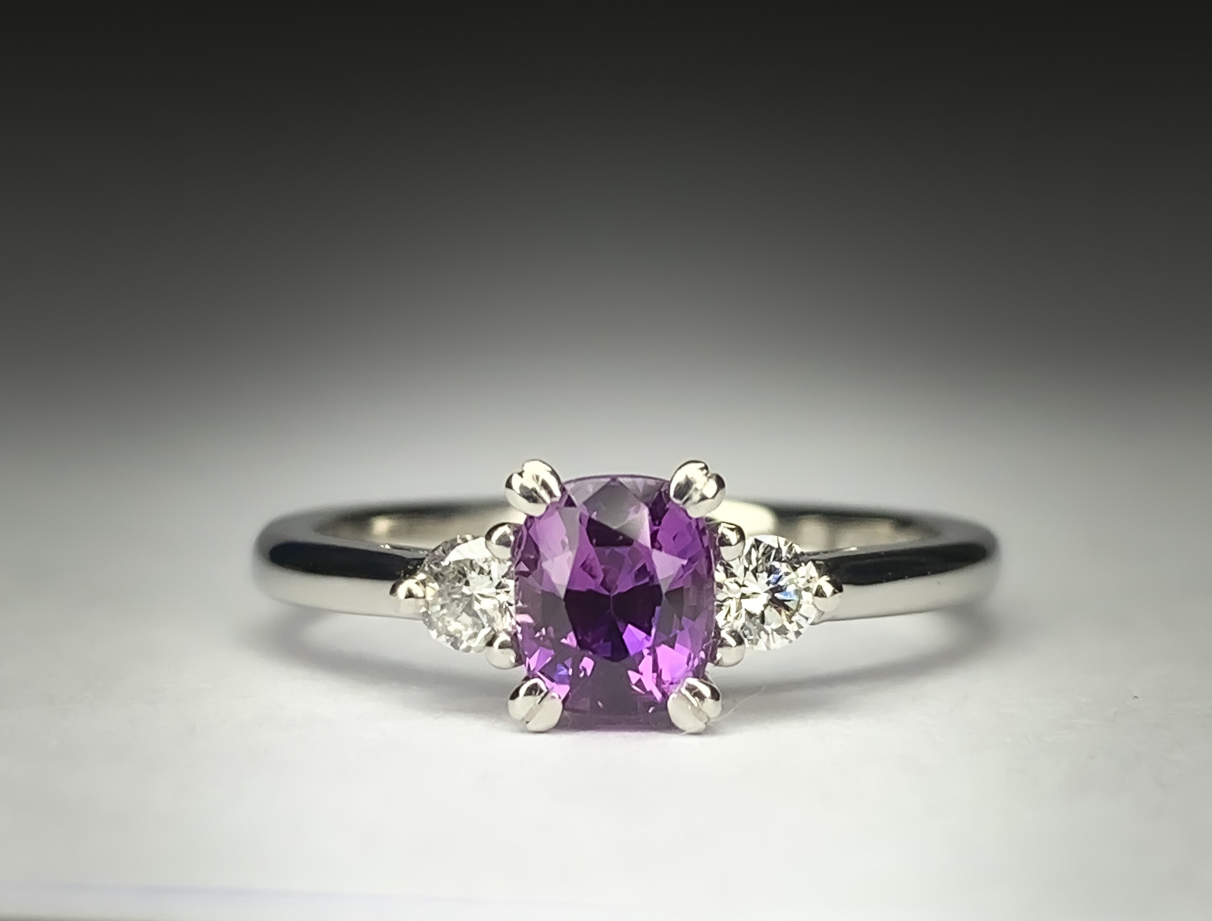 Platinum mounted diamond and 0.95ct cushion cut purple sapphire claw set ring. Made in Chichester, England.