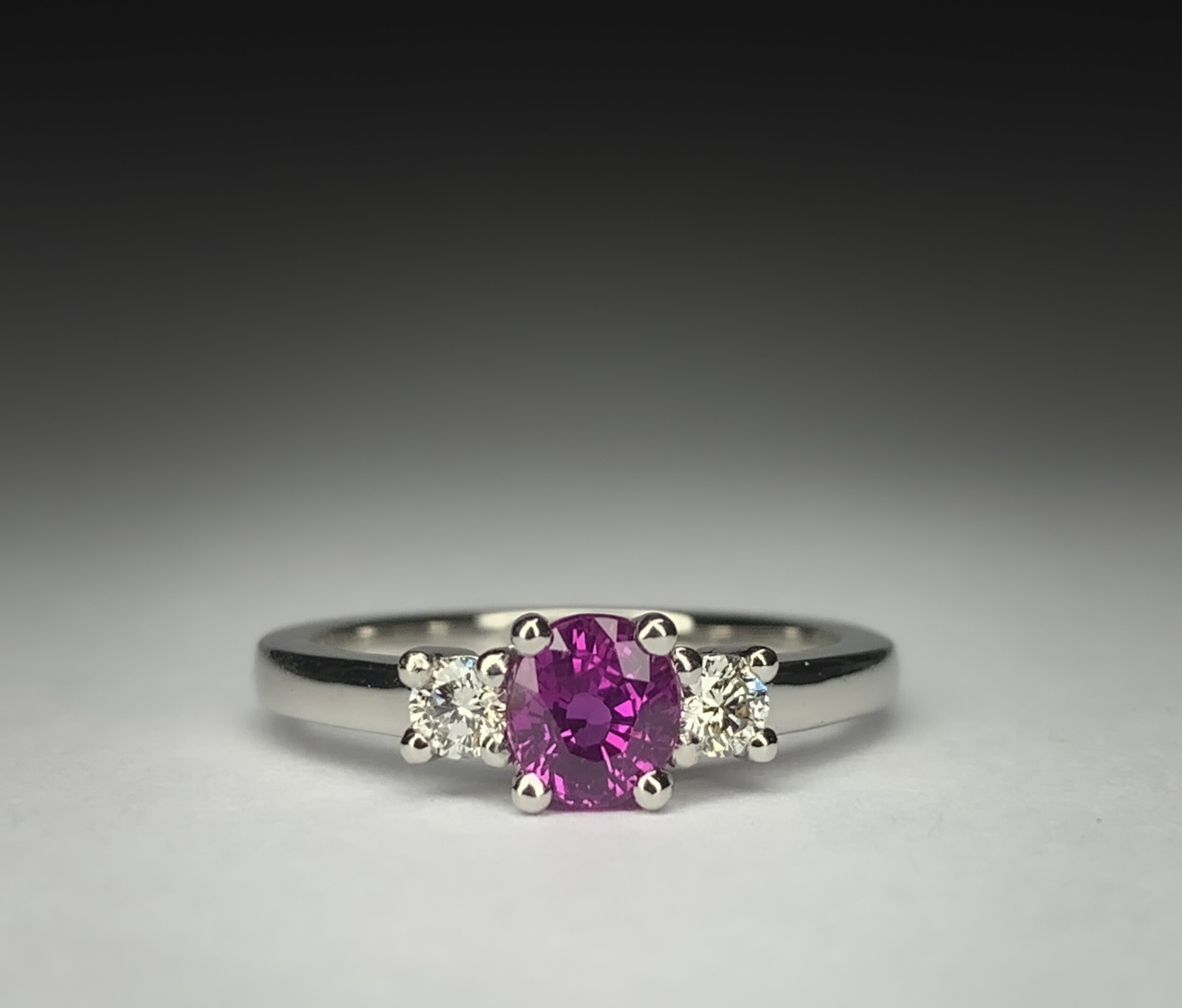 Platinum mounted 0.74ct oval pink sapphire and diamond 3 stone ring. Made in Chichester, England.