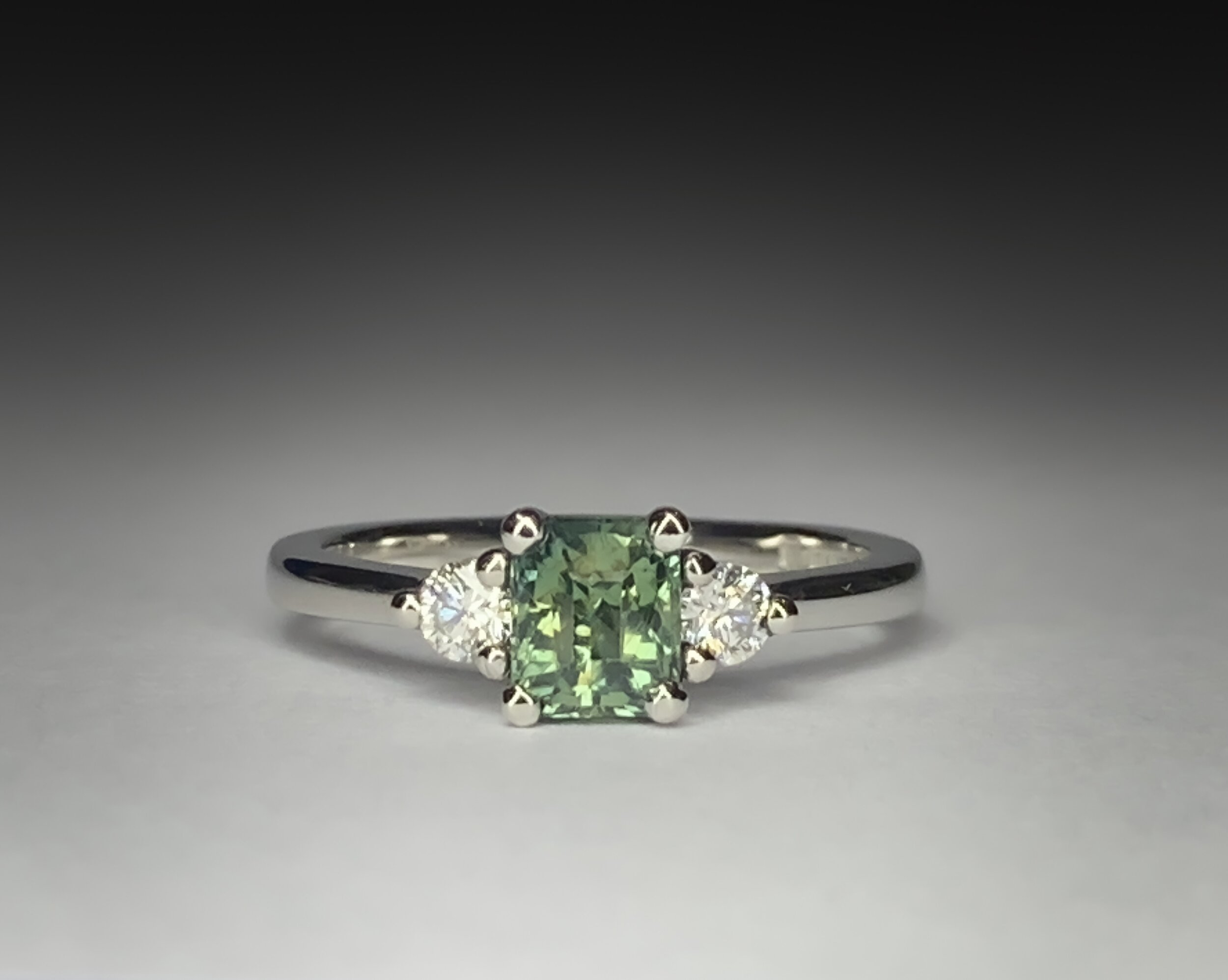 Platinum mounted diamond and 1.06ct green sapphire claw set ring. Made in Chichester, England.