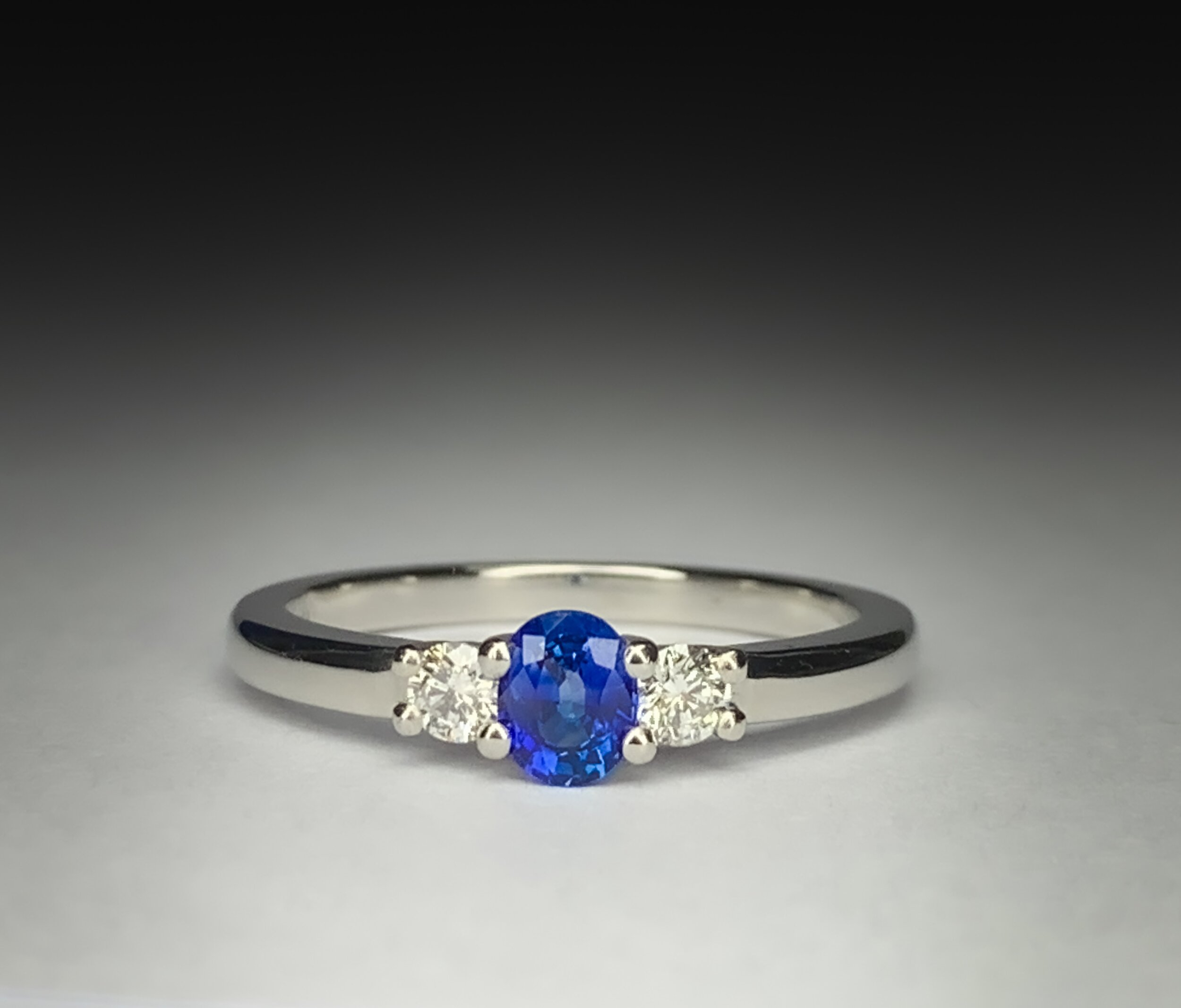 Platinum mounted diamond and 0.35ct oval blue sapphire claw set ring. Made in Chichester, England.