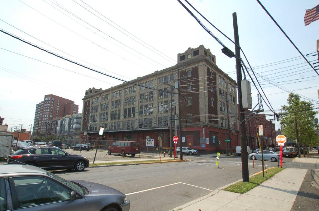 "In a flood-prone section of Hoboken, an early 20th-century ""daylight factory"" — part of the former R.B. Davis Baking Powder Company complex. The N.J. Historic Preservation Office determined this manufactory eligible for listing on the New Jersey Register of Historic Places. It was one of only three factories in the state that produced an important leavening agent for products baked in Hoboken for the all-important Northeastern U.S. consumer market. The state's first resiiency park opened in 2017 on the parking lot at the left."