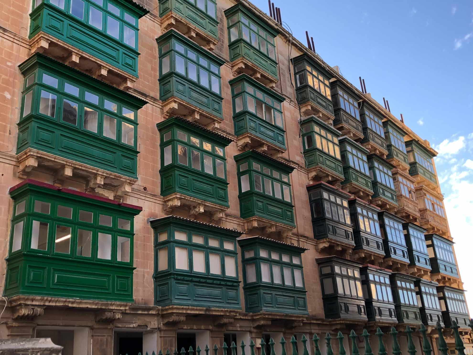 Die typischen Häuserfassaden Vallettas mit grünen Balkonen.