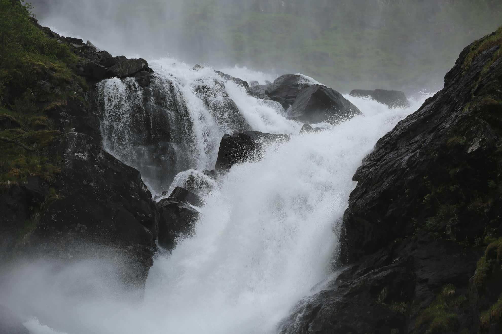 Das Wasser schießt die Felsen hinab.