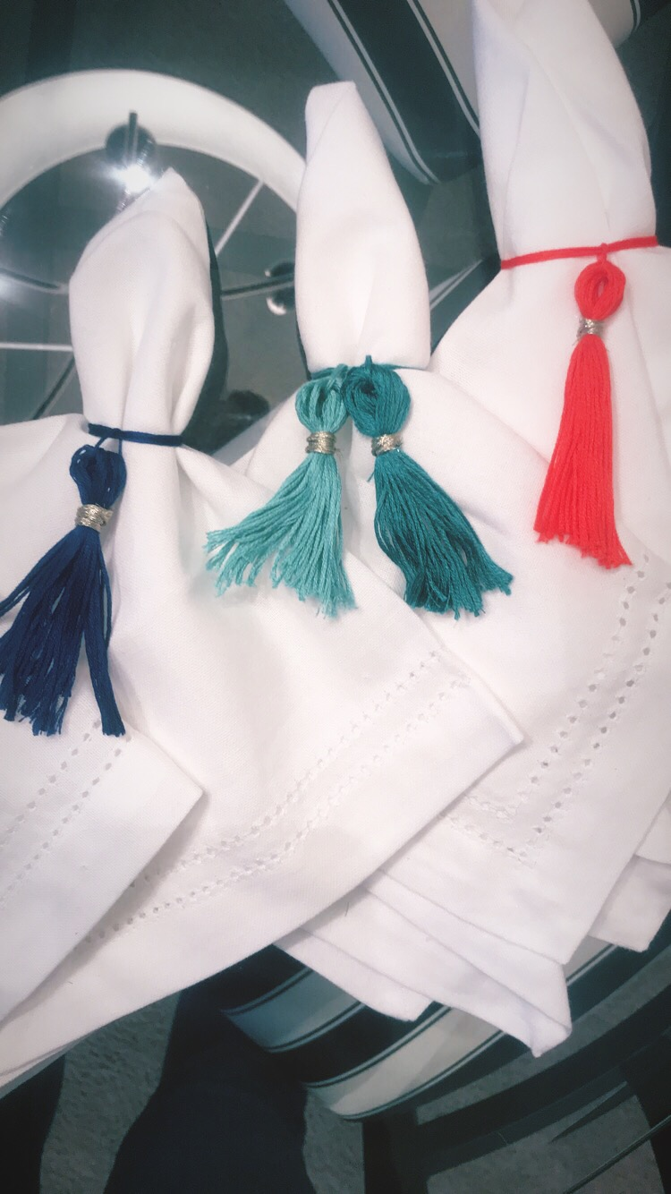 "DIY Tassel Napkin Wrings. - These are SO easy to make. Simply purchase single embroidery thread packs, cut enough thread to create the ""wring,"" and tie around the napkin. With the rest, cut the thread right through the loop to create the ""tassel."" Wrap the tassel together with your choice of material. I used gold wire. Then, tie the tassel to the wring! Easy peasy!"