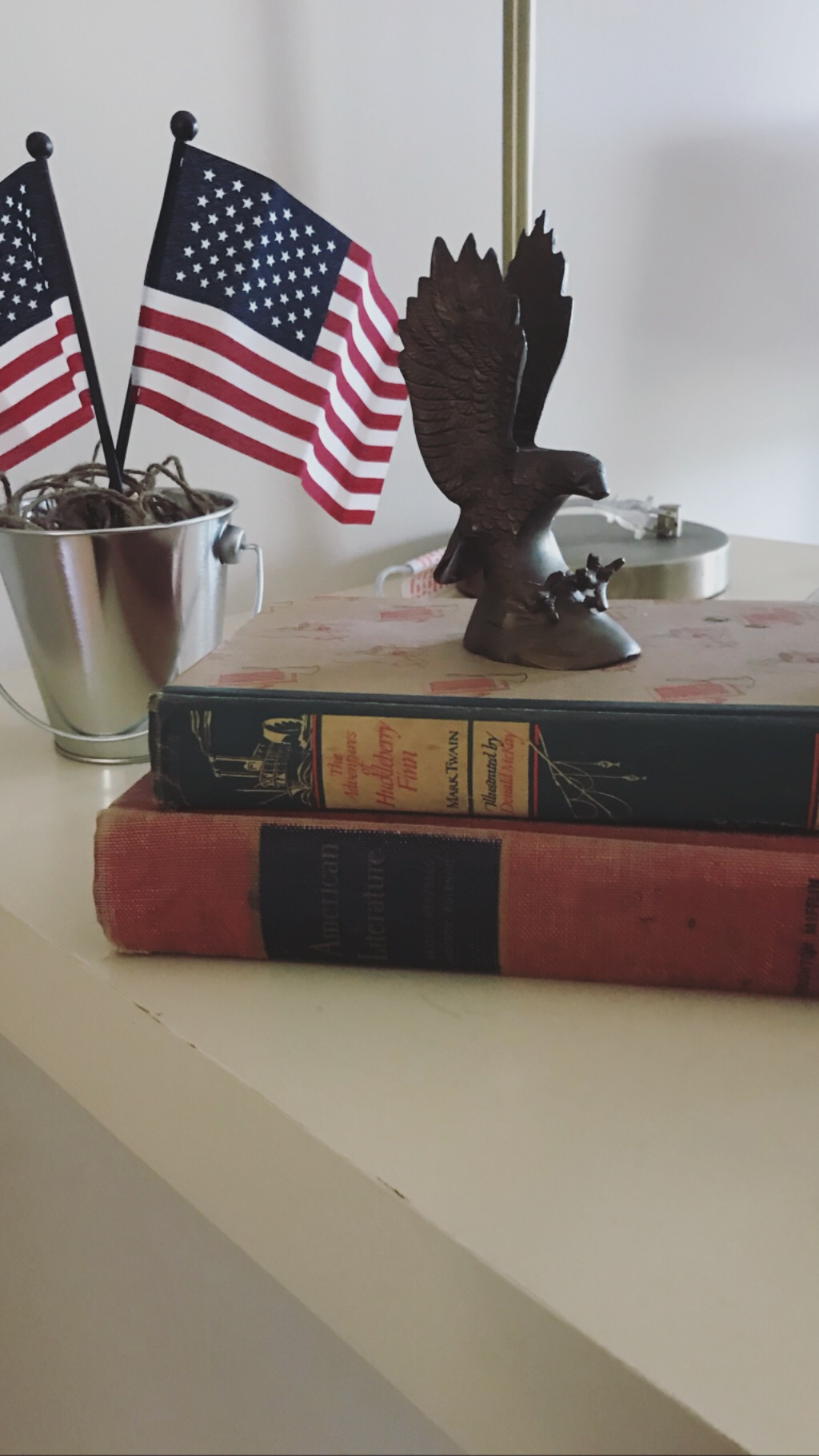 "The Adventures of Huckleberry Finn, American Literature, and brass eagle. - Collecting antique books has become almost like a sport to me. I love to search and search and find special and unique books with meaning. Finding a 1948 copy of The Adventures of Huckleberry Finn was extra special—it brought a piece of Missouri and American history to the decor.The American Literature textbook is awesome. Property of the State of Texas, it sold for $1.53 in 1941. There is writing all over the book—names, pictures, notes, love notes—right after the statement ""Pupils must not write on any page of this textbook."""