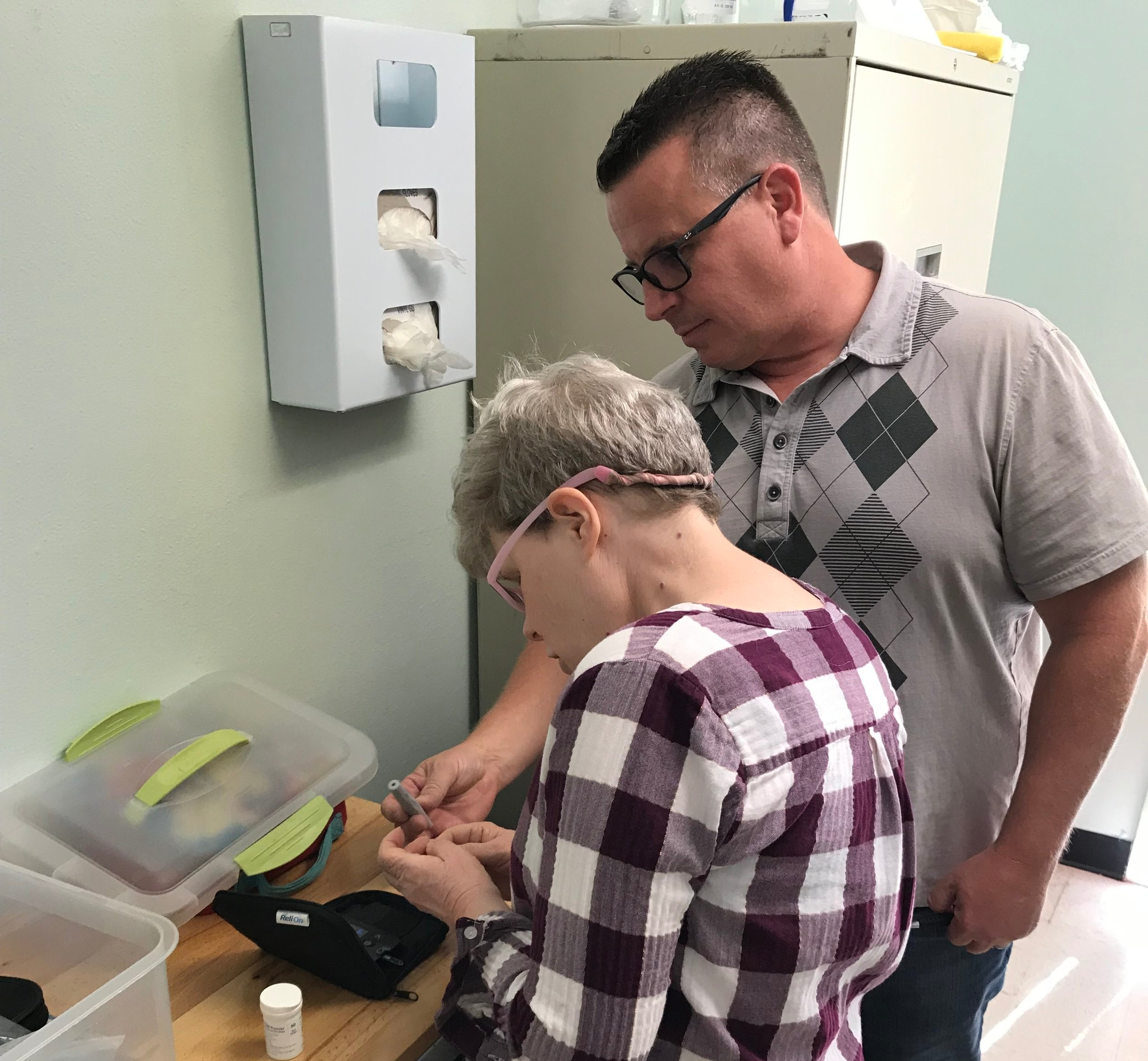Clester working with a CLIENT to take her blood sugar.