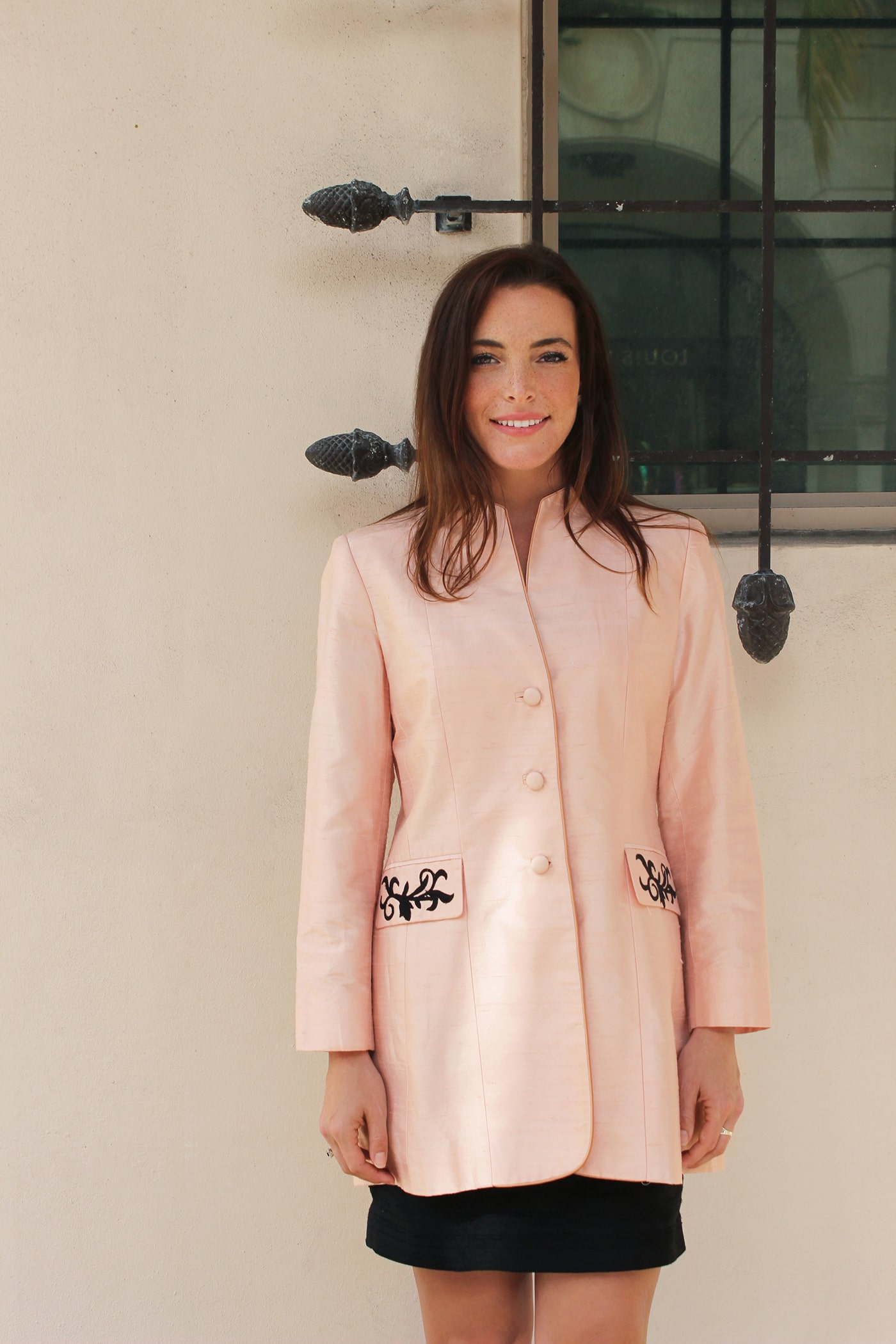 Our powder pink Crosby Jacket is made from dupioni silk and features a vine pattern in black appliqué adorning the two waist-high front pocket flaps as well as the sleeves, where it is bordered by a row of buttons on each arm.