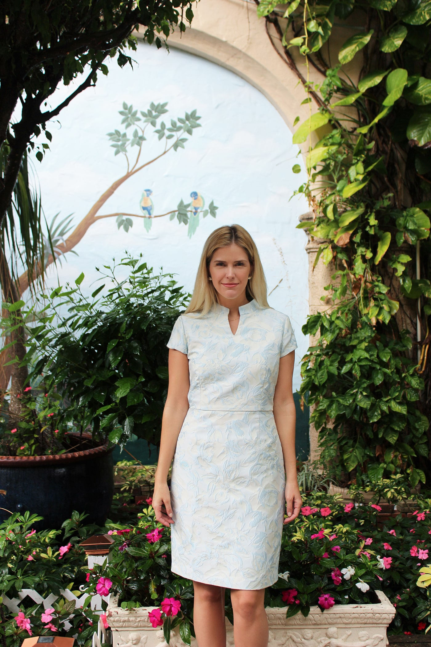 Subtle and understated, the Mona Dress is fabricated from Italian brocade that is powder-white with a baby blue floral design. With short sleeves and a petite v-neck.