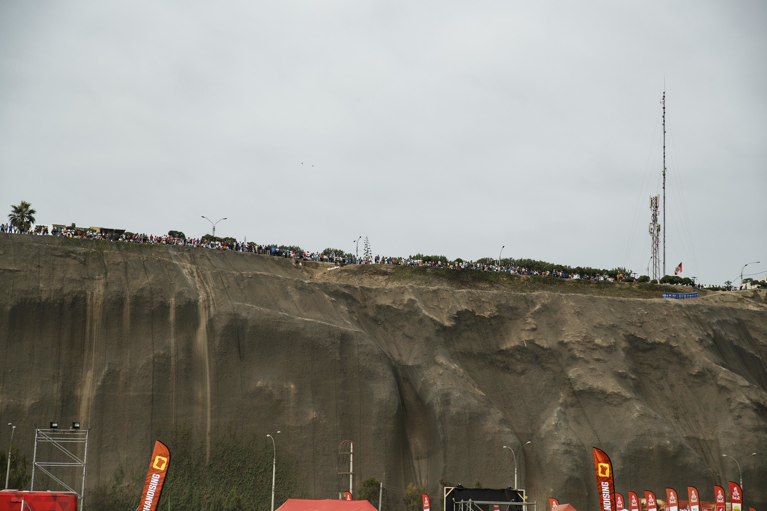 Fans line the cliffside that overlooks the beach hoping to get a view of the Podium Ceremony celebration.