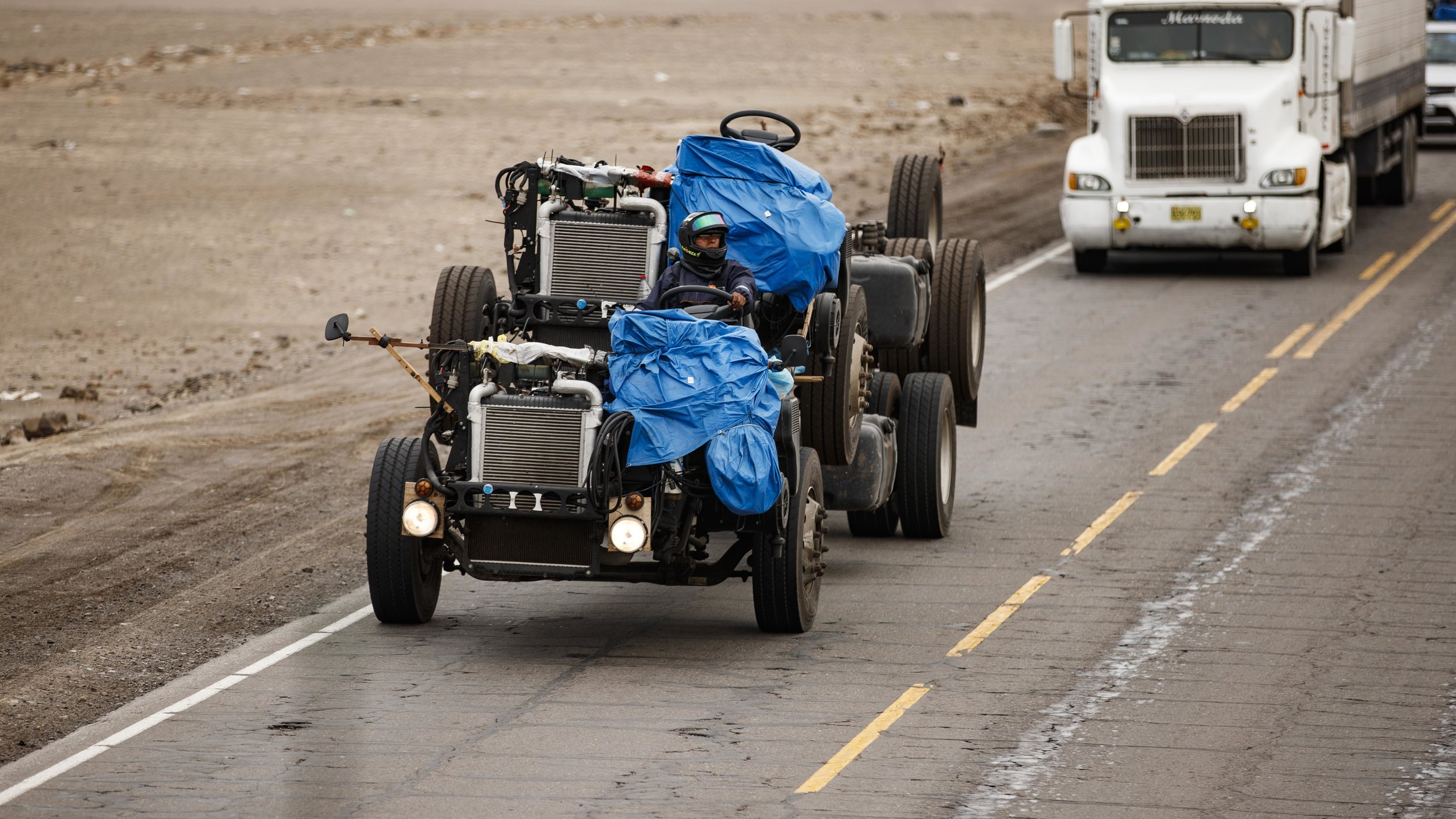 A RV chassis stacked on a RV chassis driven by a man wearing a helmet. This is one of about 6 we saw, wild.