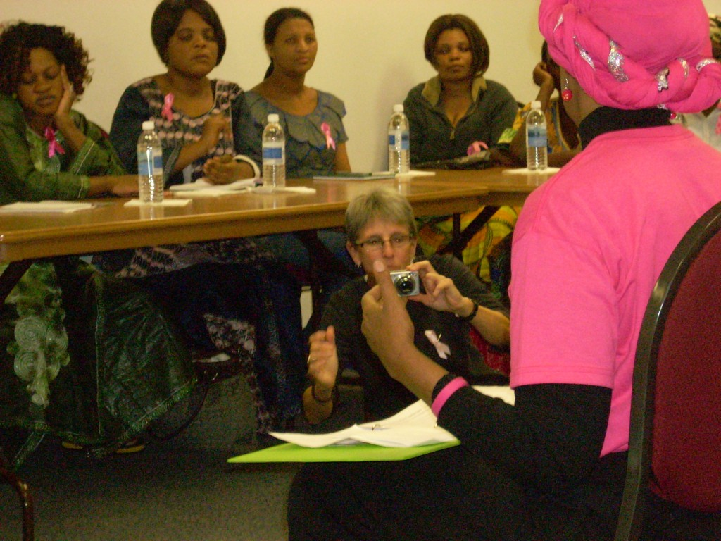 Lisa takes photos as Phillipa teaches African refugee women in Houston about breast health awareness.