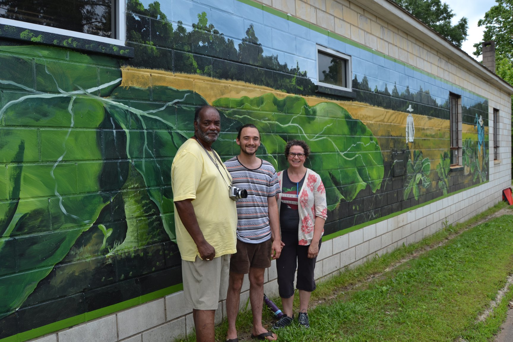 Pictured left to right: Muralist Napoleon Hill, Arts Council Board Member Alex Borst, and Working Landscapes Executive Director Carla Norwood stand in front of the mural on the Working Landscapes Produce Center, a project funded through the Grassroots Grant Program in 2018