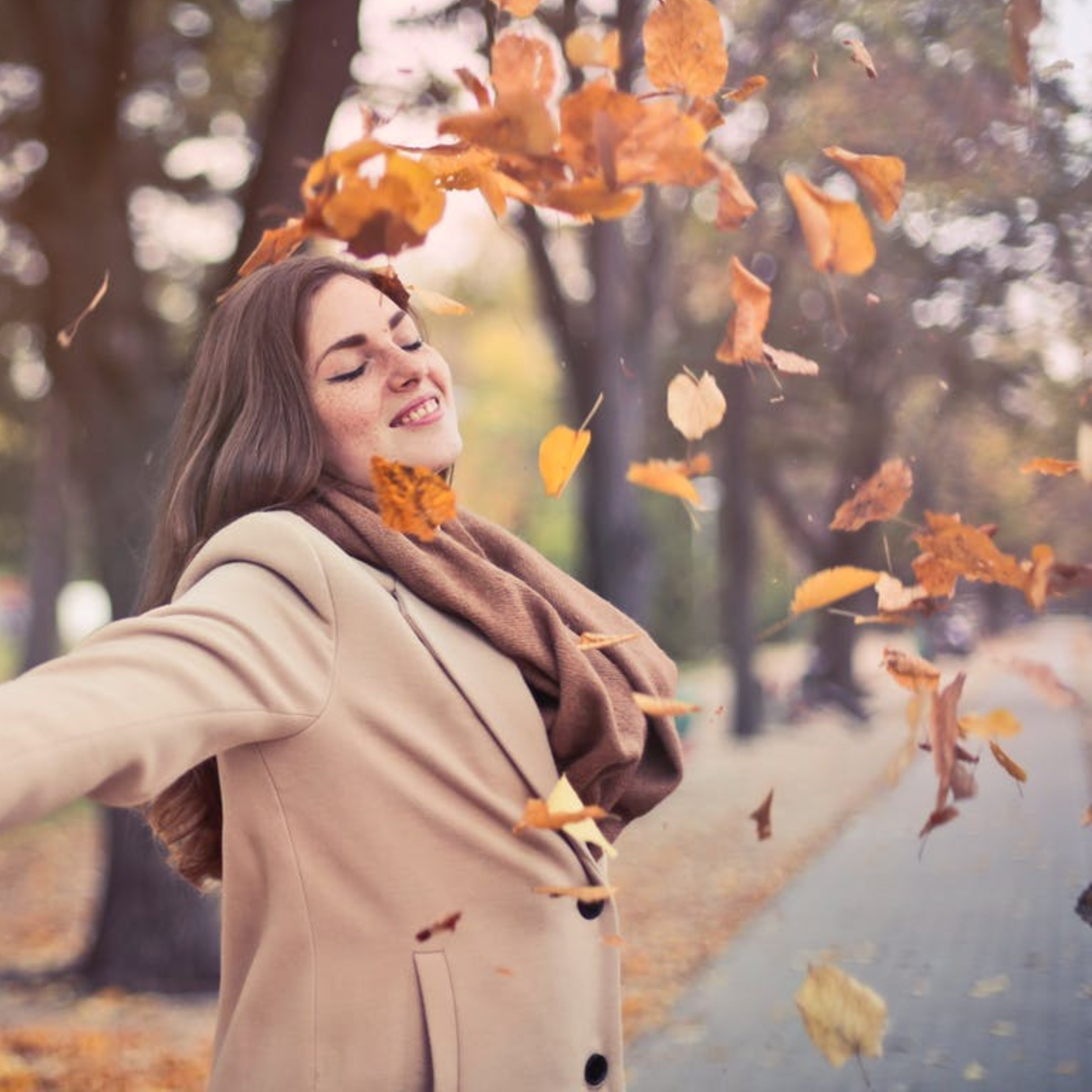 Woman-smiling-as-fall-leaves-fall-on-her.jpg
