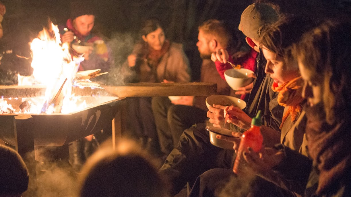 Villagers sharing a bonfire meal.