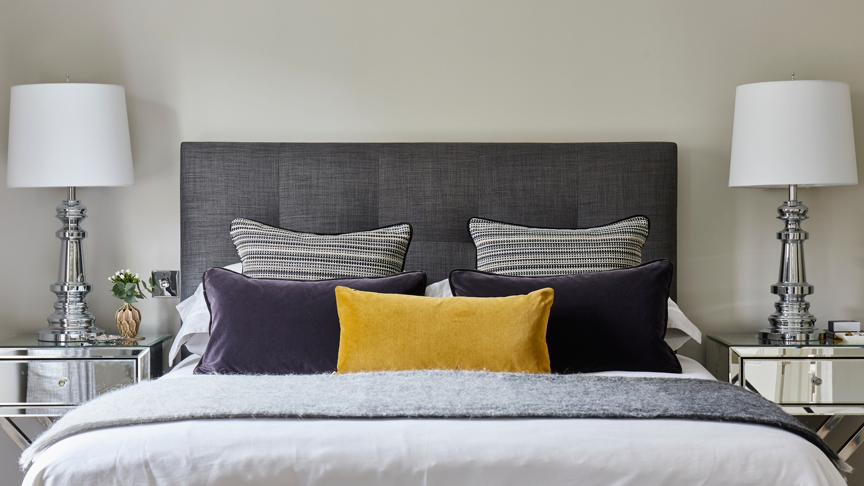 Interior designer Sonia Adams designed this master bedroom with a bespoke headboard and luxury velvet cushions