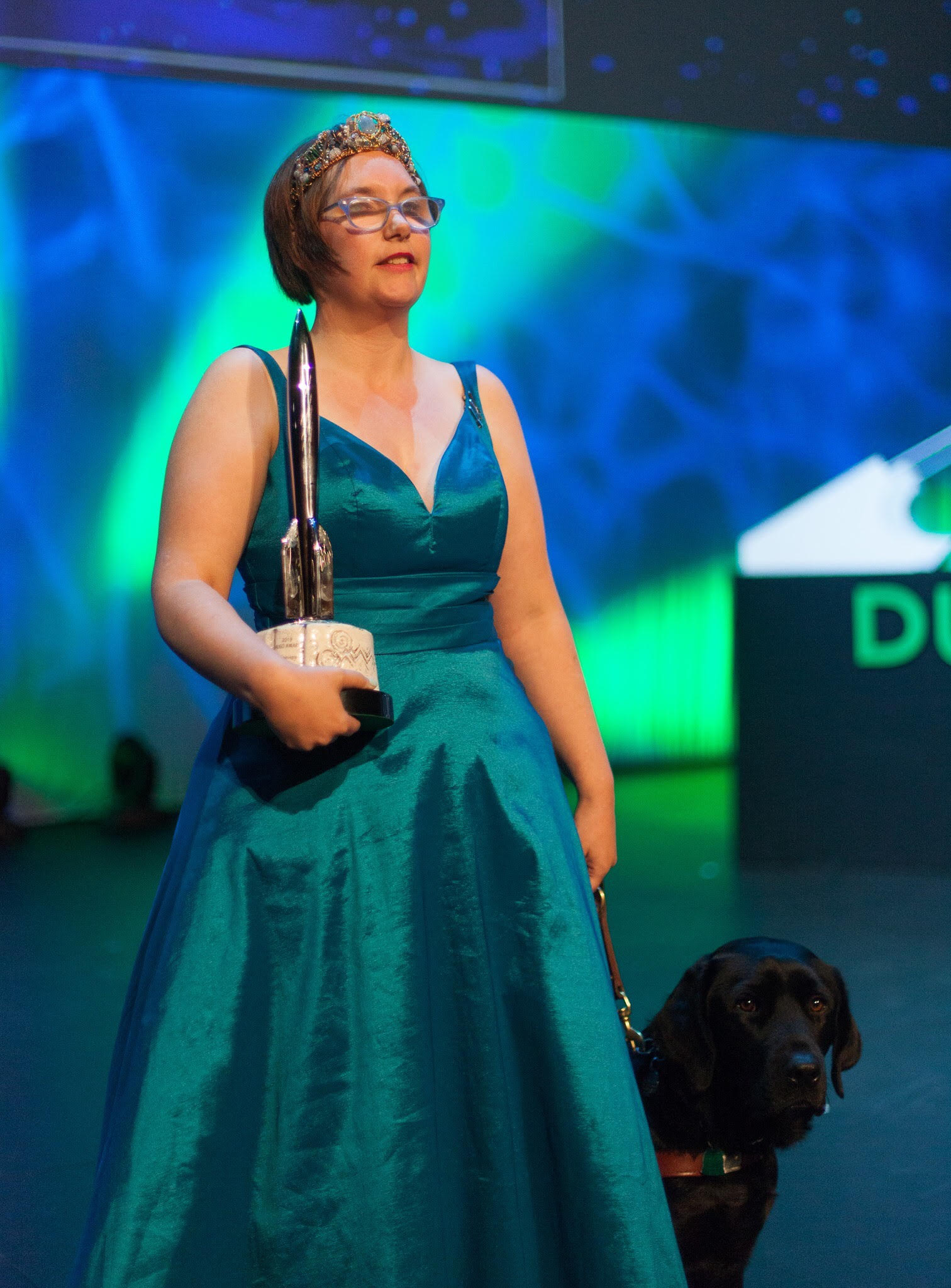 Elsa stands in a teal gown, holding a Hugo Award in the crook of her right arm, and a leash attached to a black Labrador in the left hand. Phjoto by Simon Bubb. Photo used with permission from Simon.