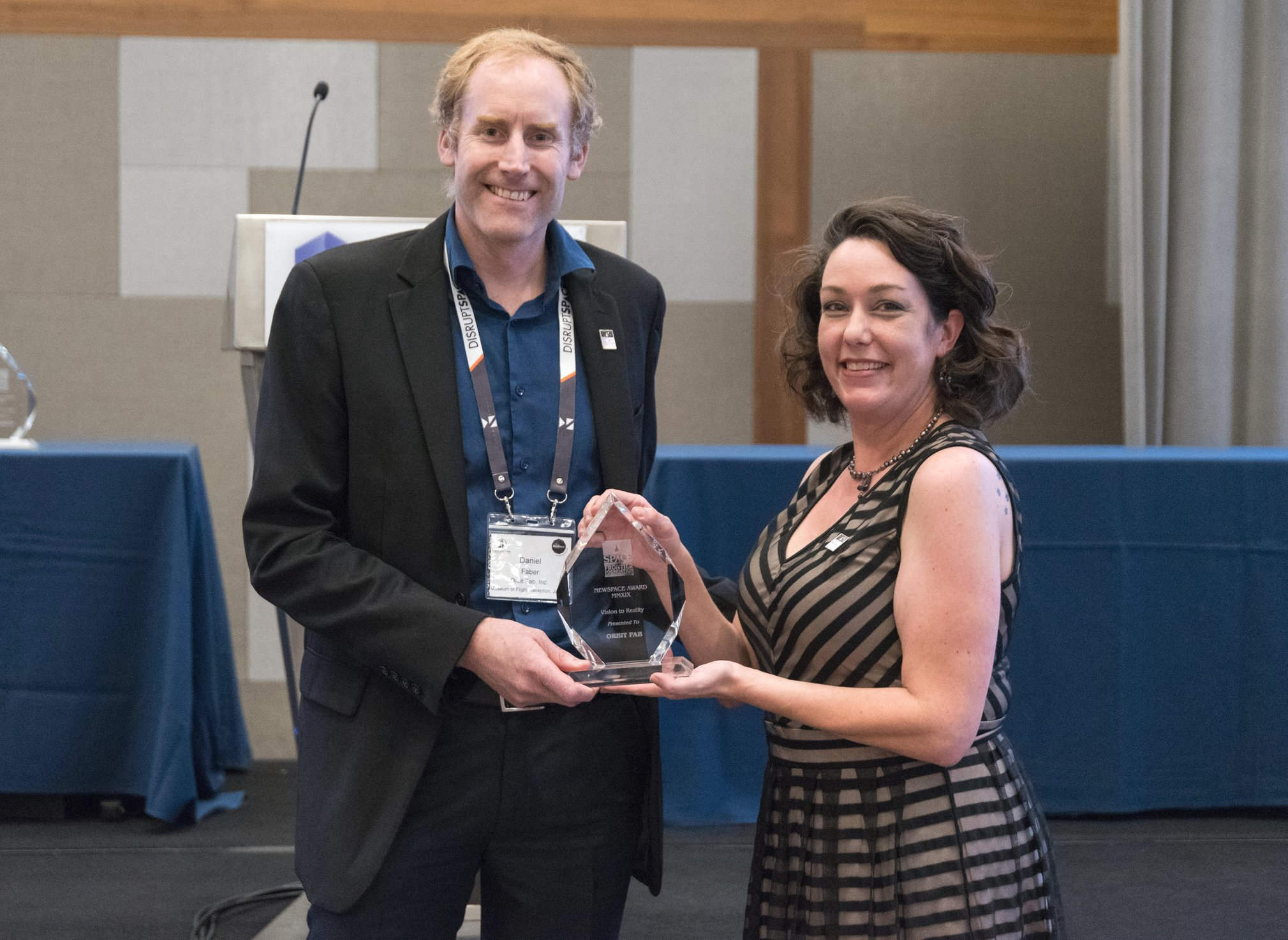 Daniel Faber, CEO of Orbit Fab (Left), receiving the Vision to Reality Award from Space Frontier Foundation board member Meagan Crawford (Right) for Orbit Fab's groundbreaking achievements during the first year of funded operations. Credit: Orbit Fab.