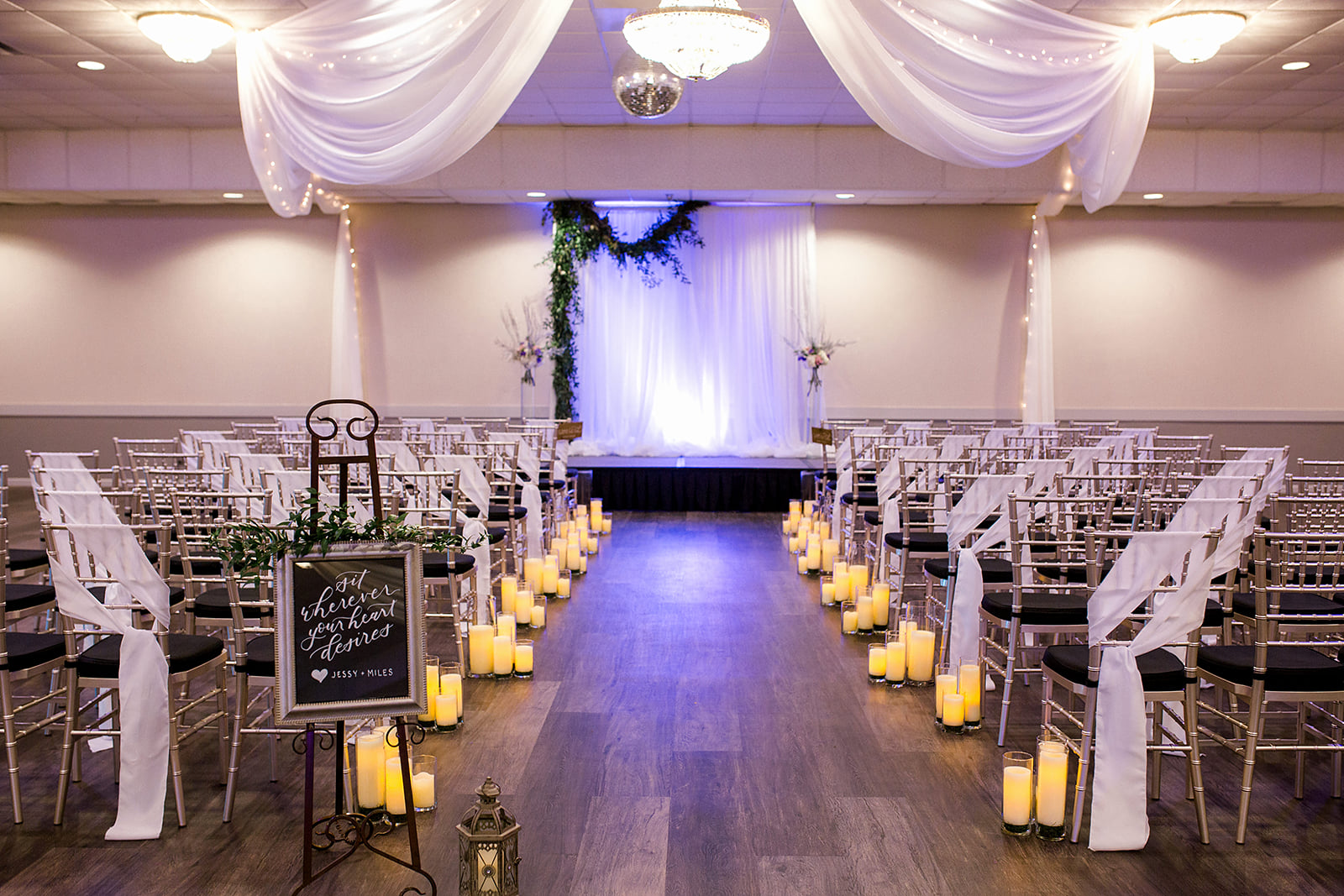 Royal Cliff banquet hall, stage with pipe and drape ceremony backdrop for indoor ceremony with candles