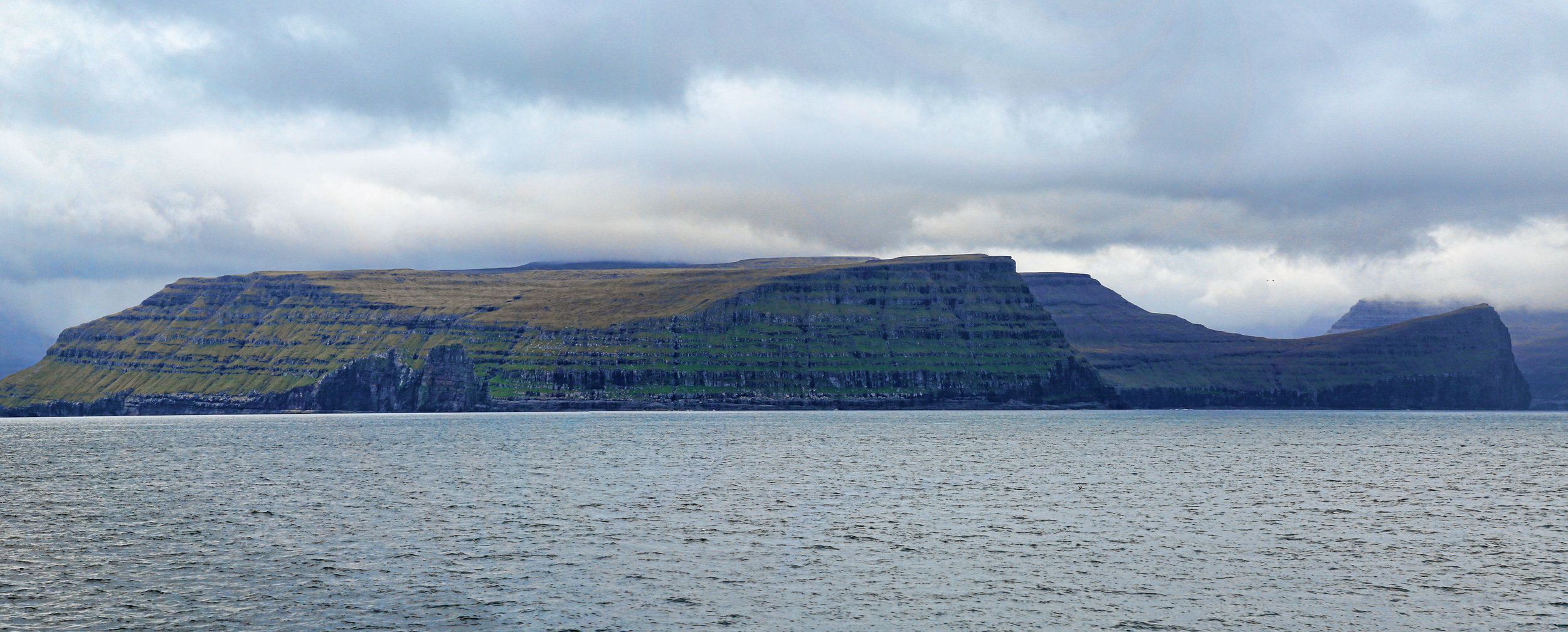The Faroe Islands are a pile of Paleogene-age basalts, deeply cut by magnificent fjords.