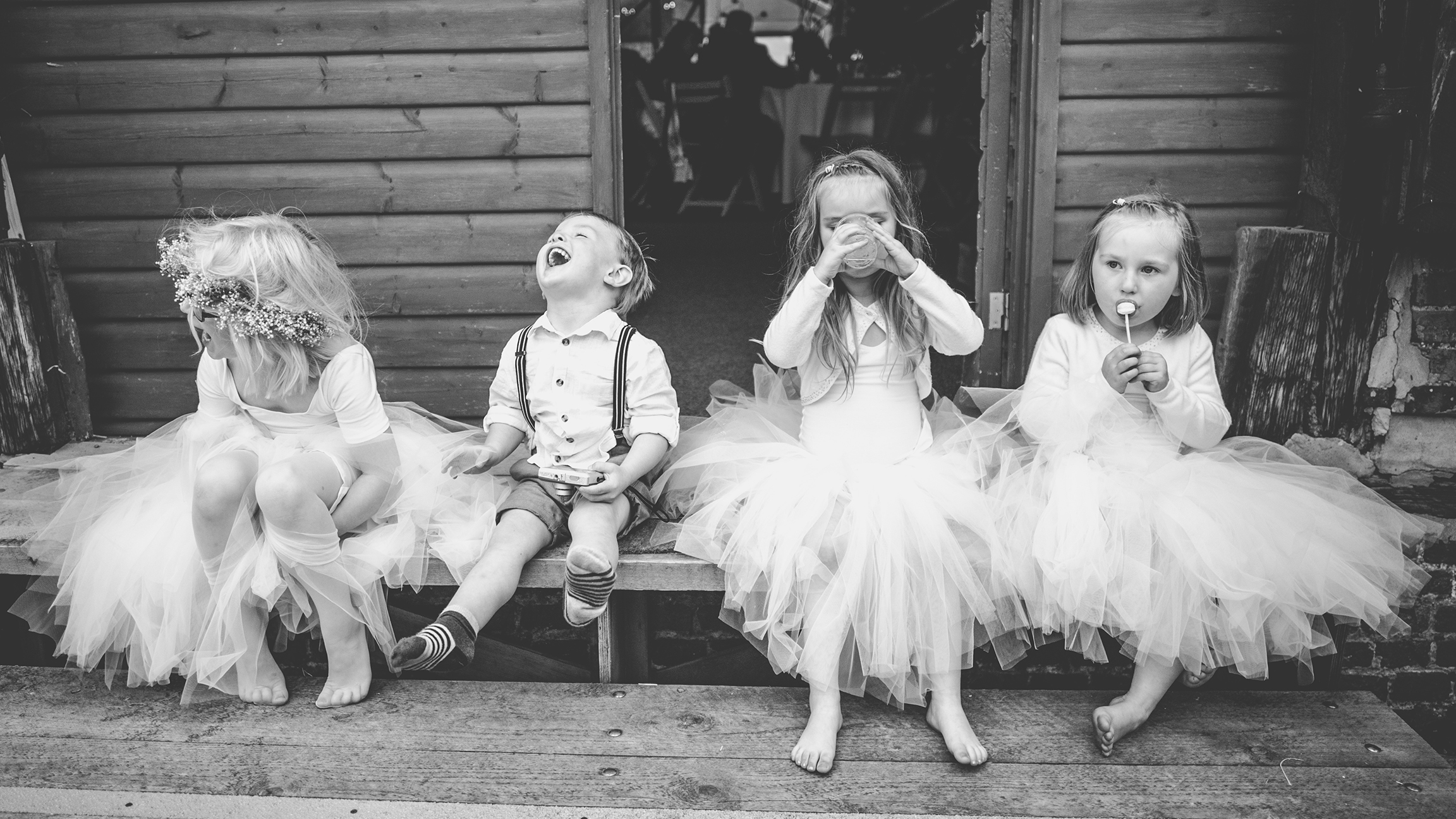 Three flower girls and a page boy sitting on a step, unaware of camera as they laugh eat and drink. Yorkshire wedding photographer.